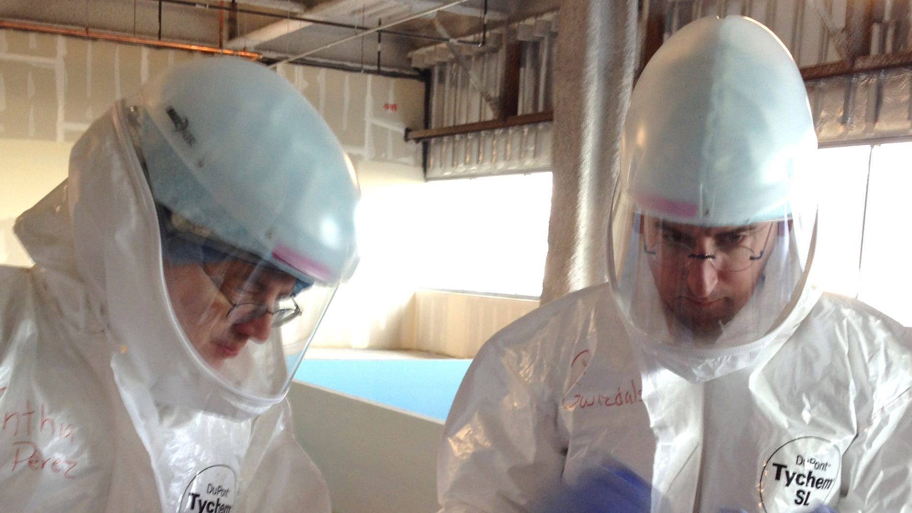In this Monday, Oct. 6, 2014, photo Dr. Michael OConnor , left, and Dr. Mark Nunnally, learn how to use personal protective gear during Ebola preparedness training at the University of Chicago. (AP Photo/Lindsey Tanner)