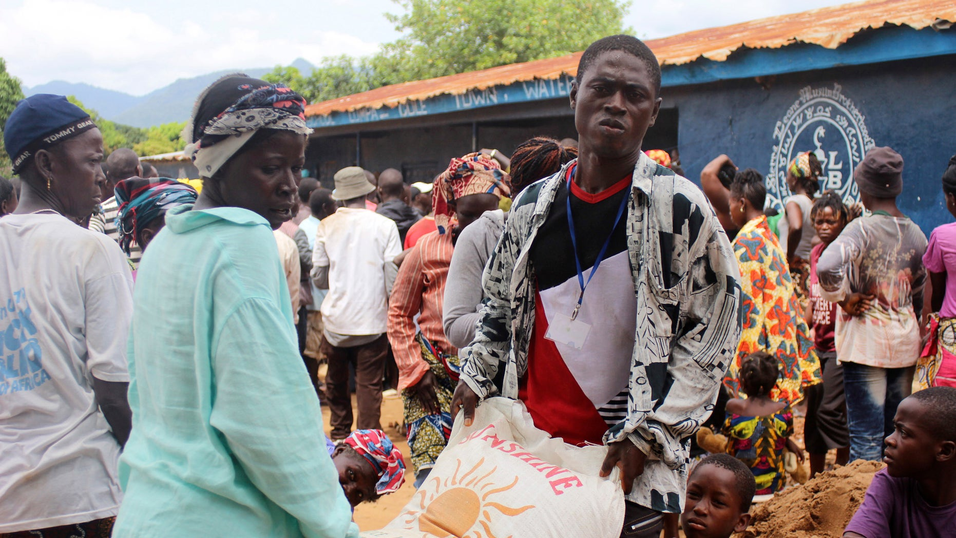 People carry a bag of rice at a World Food Programme distribution point in Freetown October 18, 2014. The U.N.'s World Food Programme and Food and Agriculture Organisation say border and market closures, quarantines and movement restrictions, and widespread fear of Ebola have led to food scarcity, panic buying and price increases, especially in Sierra Leone and Liberia. The WFP is trying to provide food to around 1 million people in the three worst-affected countries. REUTERS/Josephus Olu-Mamma