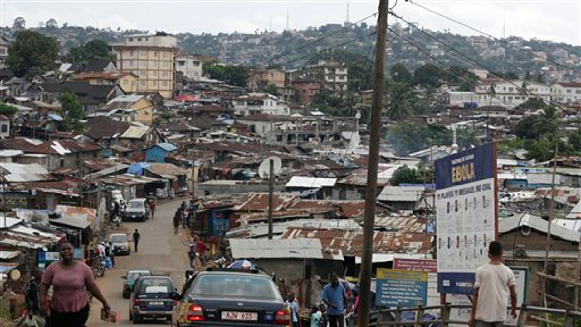 In this photo taken Thursday, Aug. 13, 2015, a billboard advises people how to keep free of Ebola, in a shanty town on the outskirts of Freetown, Sierra Leone, as people in the nearby village of Massessehbeh are finally released from Ebola quarantine, after Sierra Leone President Ernest Bai Koroma cut a tape to release the quarantine in the village. (AP Photo/Sunday Alamba)