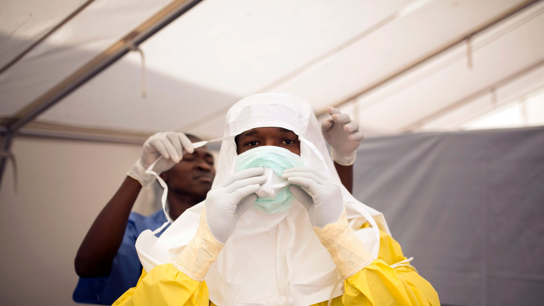 Health workers put on protective gear before entering a quarantine zone at a Red Cross facility in the town of Koidu, Kono district in Eastern Sierra Leone December 19, 2014. REUTERS/Baz Ratner