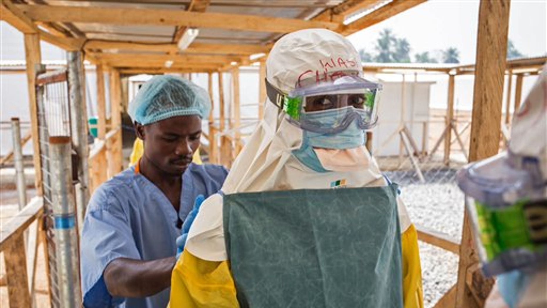 In this photo taken on Monday, March 2,  2015, a health care worker prepares a colleague's virus protective gear before entering a high risk zone at an Ebola virus clinic operated by the International Medical Corps in Makeni, Sierra Leone. (AP Photo/ Michael Duff)