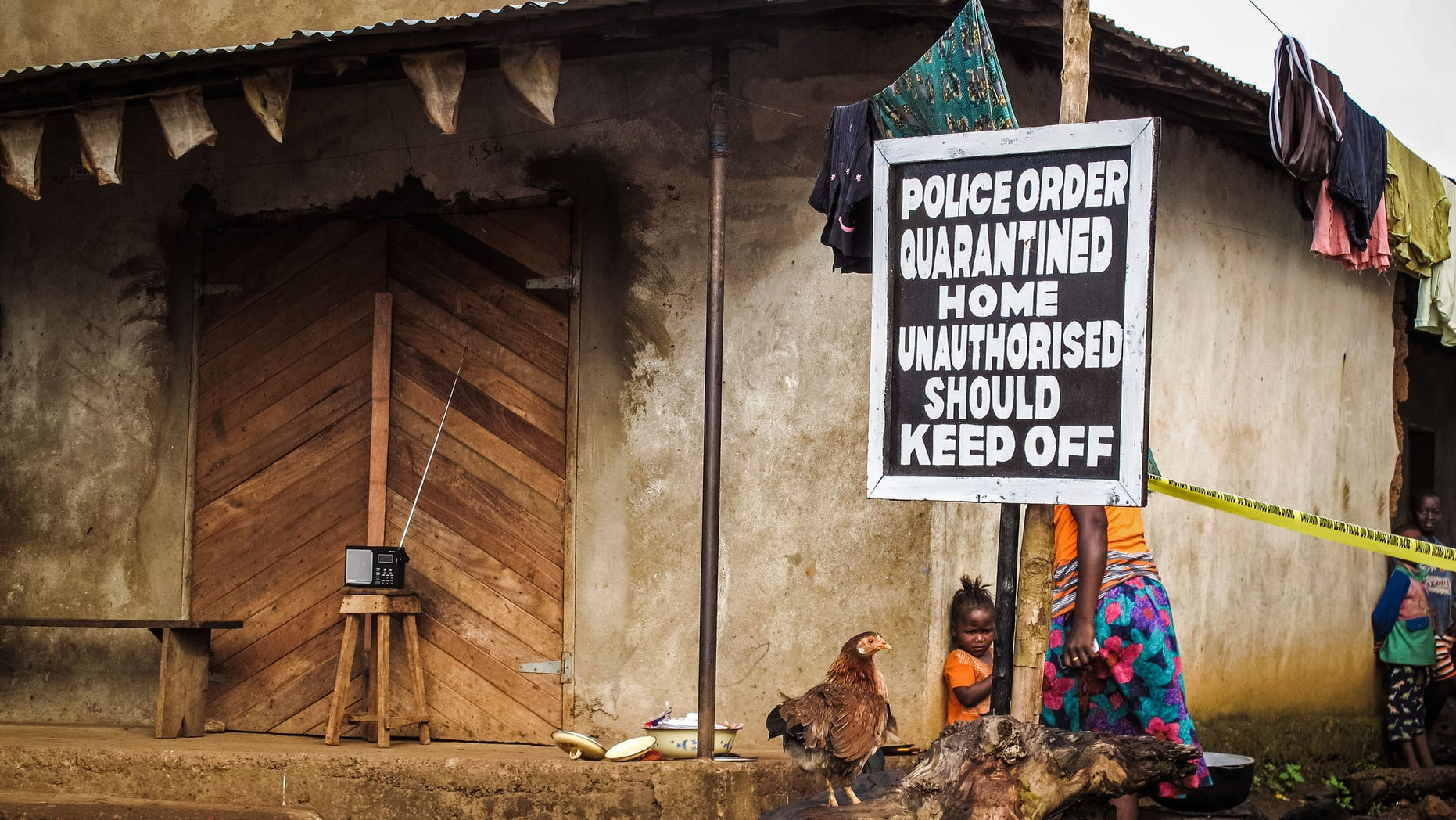 In this file photo taken on Wednesday, Oct. 22, 2014, A child, center, stands underneath a signboard as a family home is placed under quarantine due to the Ebola virus in Port Loko, Sierra Leone. (AP Photo/Michael Duff, File)