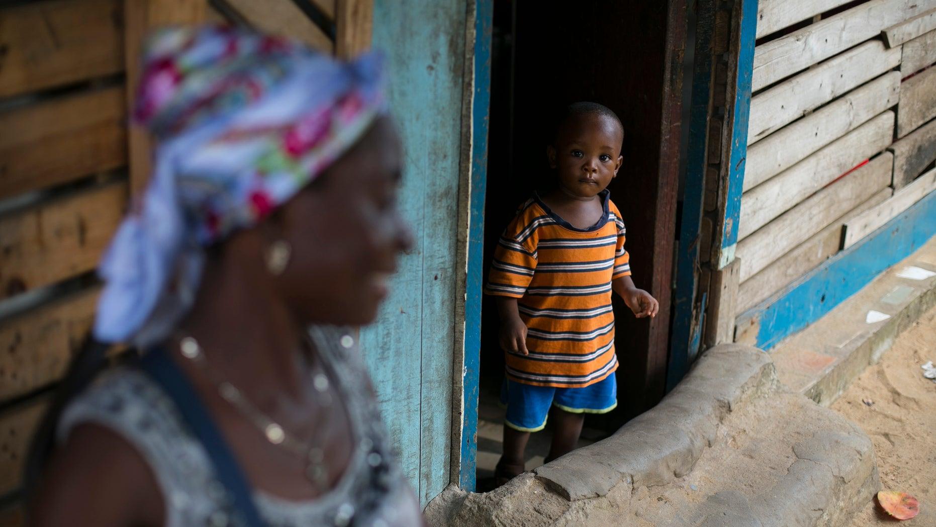 A Sierra Leonean boy looks out of a doorway in Freetown, Sierra Leone, December 16, 2014. REUTERS/Baz Ratner