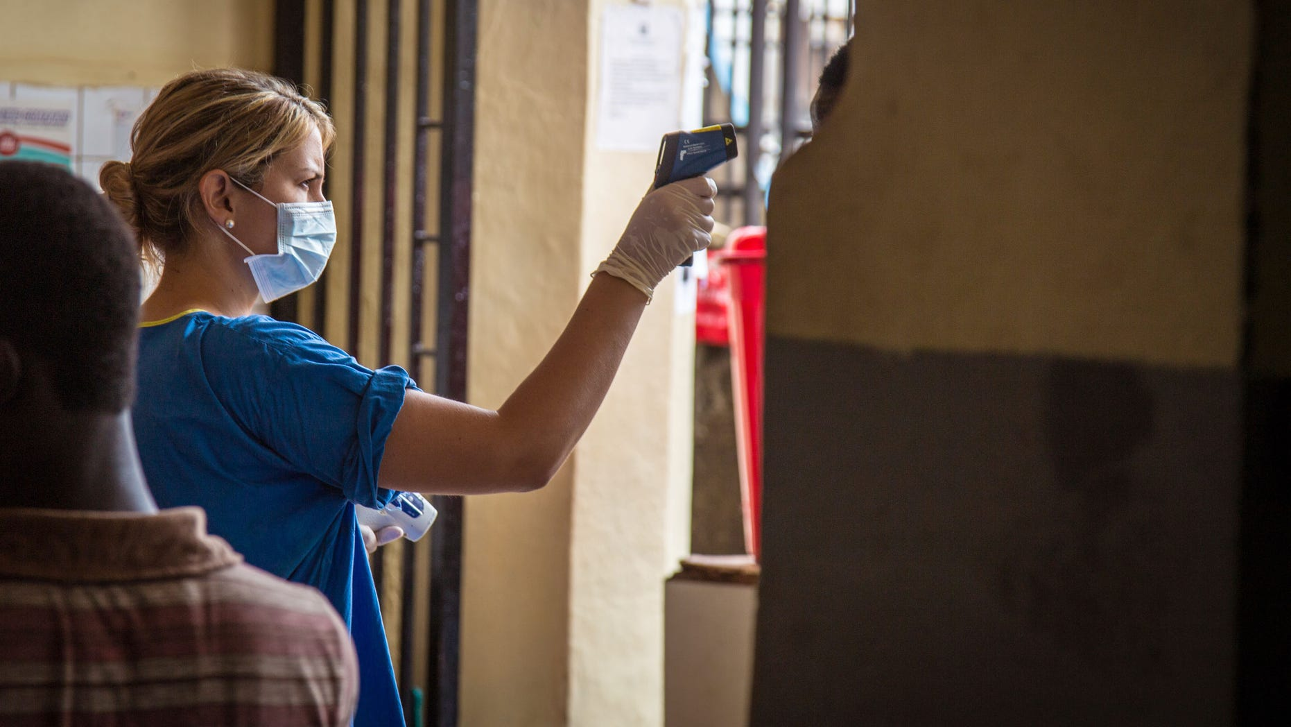 In this photo taken on Friday, Aug. 29, 2014, a health worker measures a patient's temperature at the Connaught Hospital, which has suffered the loss of medical workers in the past from the Ebola virus, in Freetown, Sierra Leone.  (AP Photo/ Michael Duff)