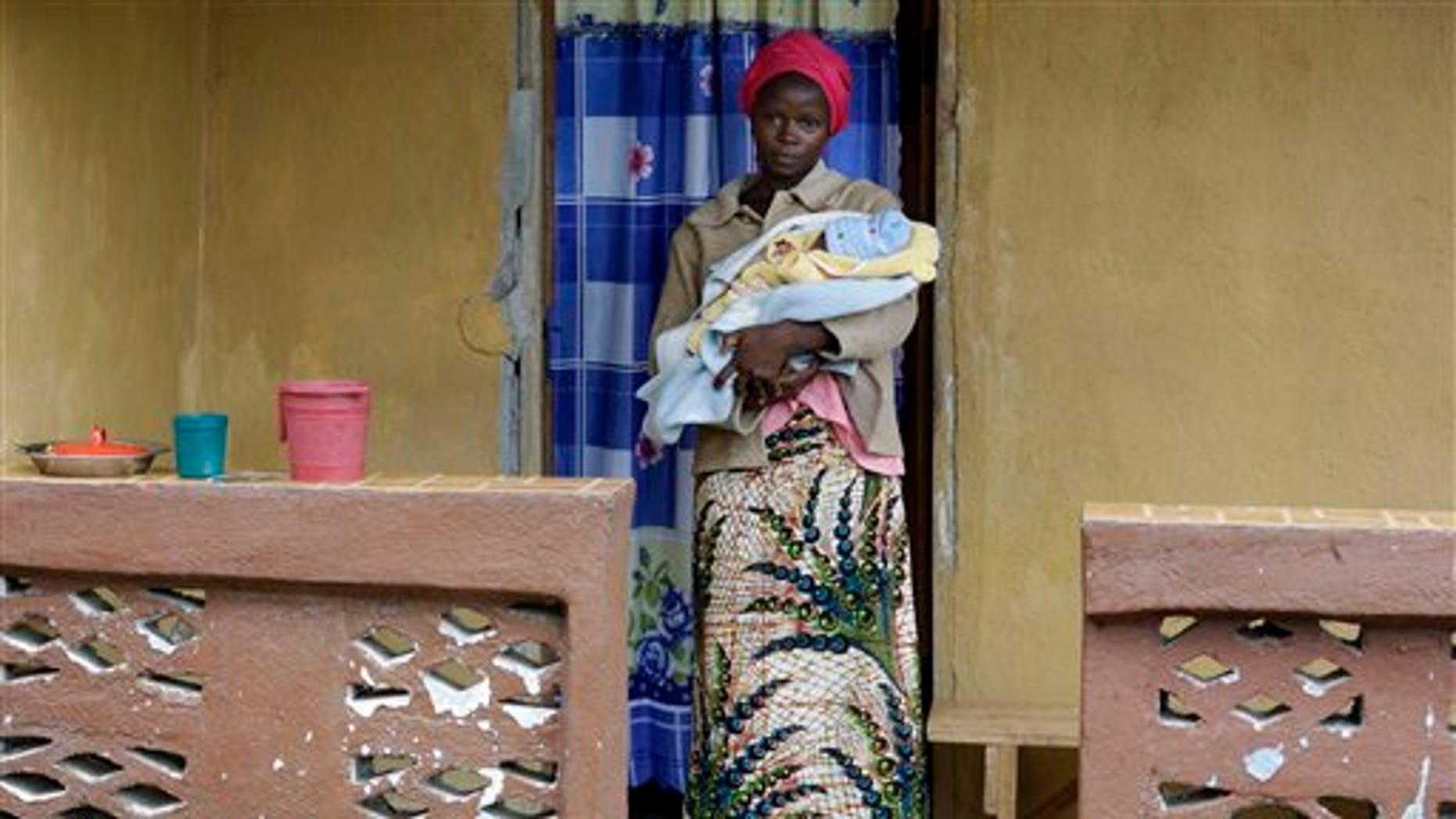 In this Sunday, Aug. 16, 2015 file photo, Ebola survivor Victoria Yillia stands with her newborn son Barnabas outside her home in Kenema, on the outskirts of Freetown, Sierra Leone. (AP Photo/Sunday Alamba file)