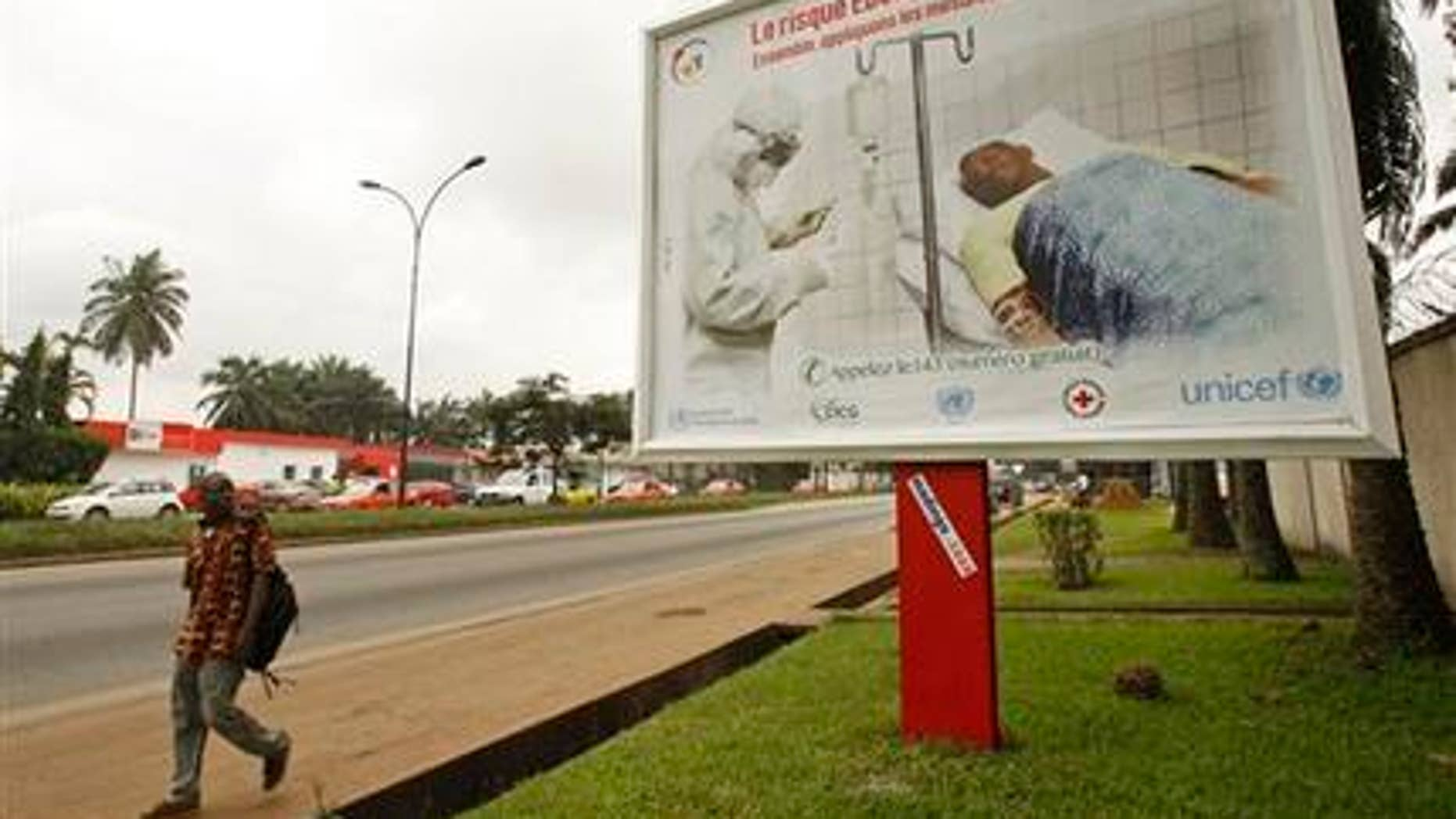 Aug. 25, 2014: A man, left, walk past a Ebola awareness campaign poster, in the city of Abidjan, Ivory Coast.