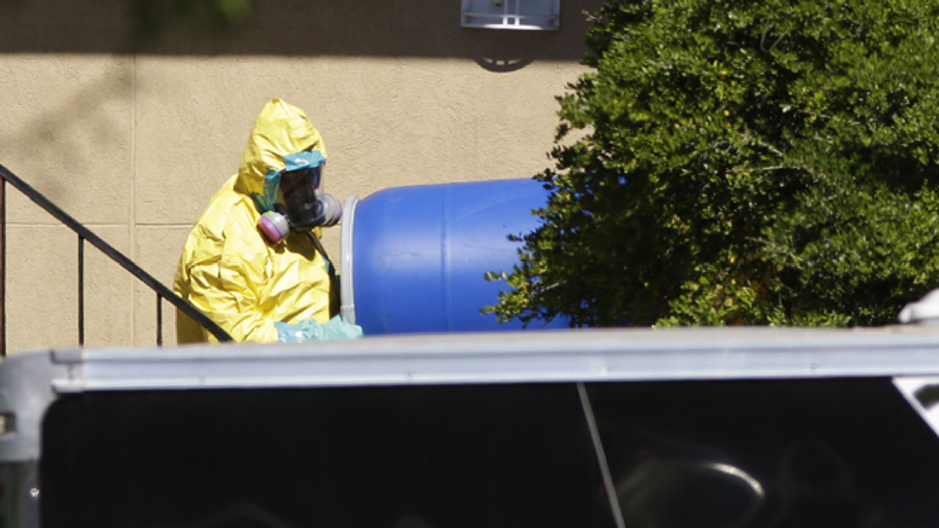 Oct. 3, 2014: A hazardous material cleaner removes a blue barrel from the apartment in Dallas. (AP)