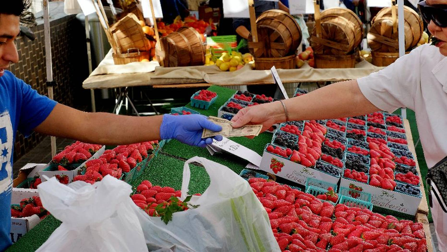 In this Friday, Feb. 6, 2015 photo, a shopper pays for produce at a Farmers Market in downtown Los Angeles. The Commerce Department releases its January report on consumer spending, which accounts for 70 percent of economic activity, on Monday, March 2, 2015. (AP Photo/Richard Vogel)