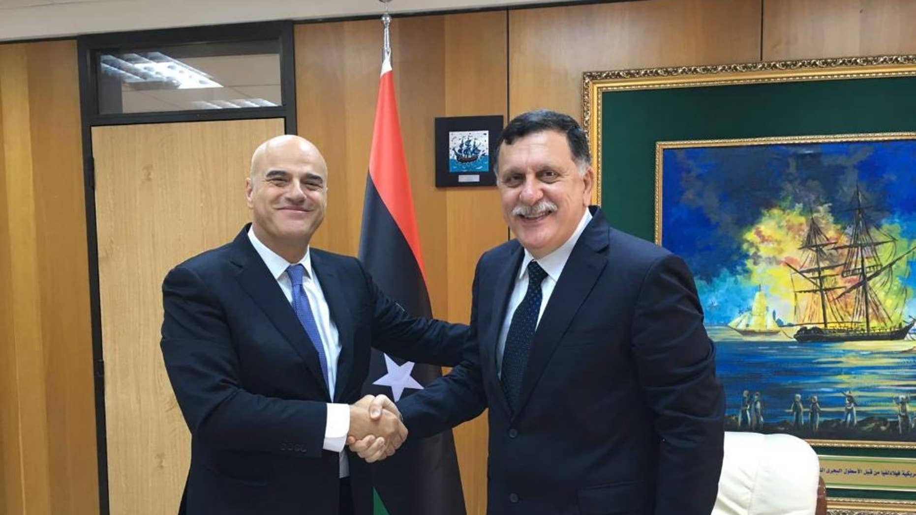 Italian oil giant Eni CEO Claudio Descalzi, left, and and Libya's new prime minister, Fayez al-Serraj shake hands in Tripoli, Libya, Saturday, June 4, 2016. The CEO of Italian oil giant Eni has traveled to Tripoli for the first time since July 2014 to meet with the new head of Libya's U.N.-backed government. Eni said in a statement that the meeting Saturday underlined Eni's commitment to continuing operations in Libya and to support the National Oil Corporation's efforts to increase production. (ENI via AP)