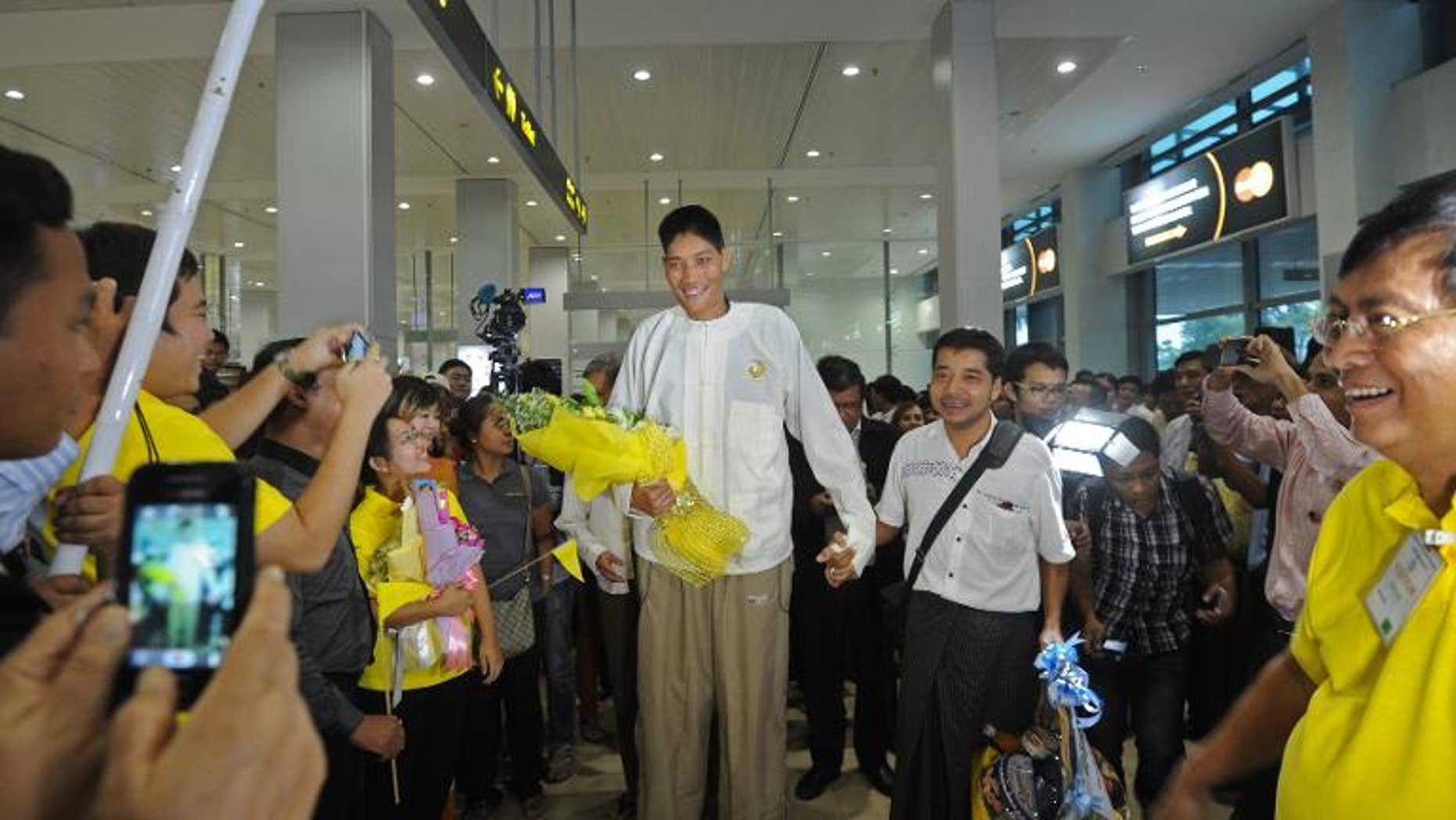 Win Zaw Oo (C) arrives from Singapore, at Yangon airport on September 26, 2013. At seven foot eight inches (233cm), Win Zaw Oo is believed to be the country's tallest man and arrived in Yangon after undergoing successful brain surgery.