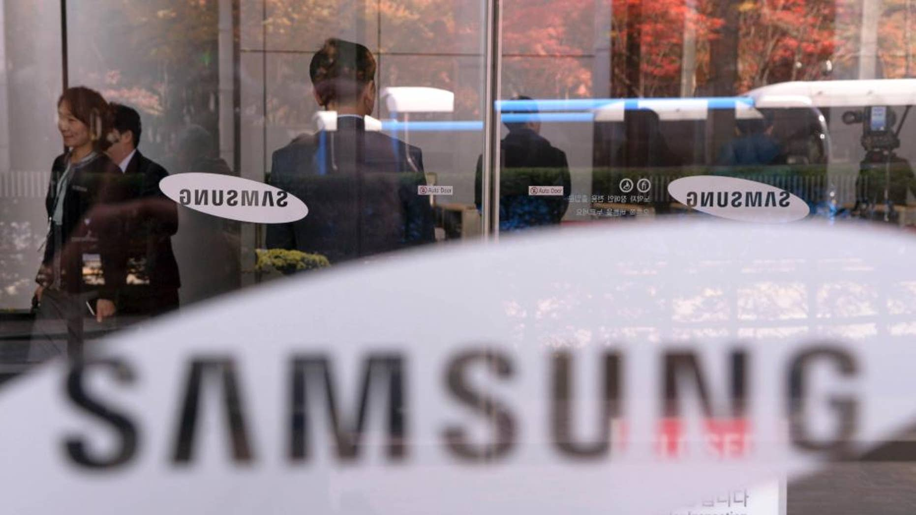 Employees walk past logos of Samsung Group at its headquarters in Seoul, South Korea, Wednesday, Nov. 23, 2016. South Korean prosecutors investigating a corruption scandal surrounding the country's president and her friend raided on Wednesday a unit of the country's largest business group, Samsung, and the national pension fund, as public outrage grows over Samsung's alleged link with the scandal. (Jang Se-young/Newsis via AP)