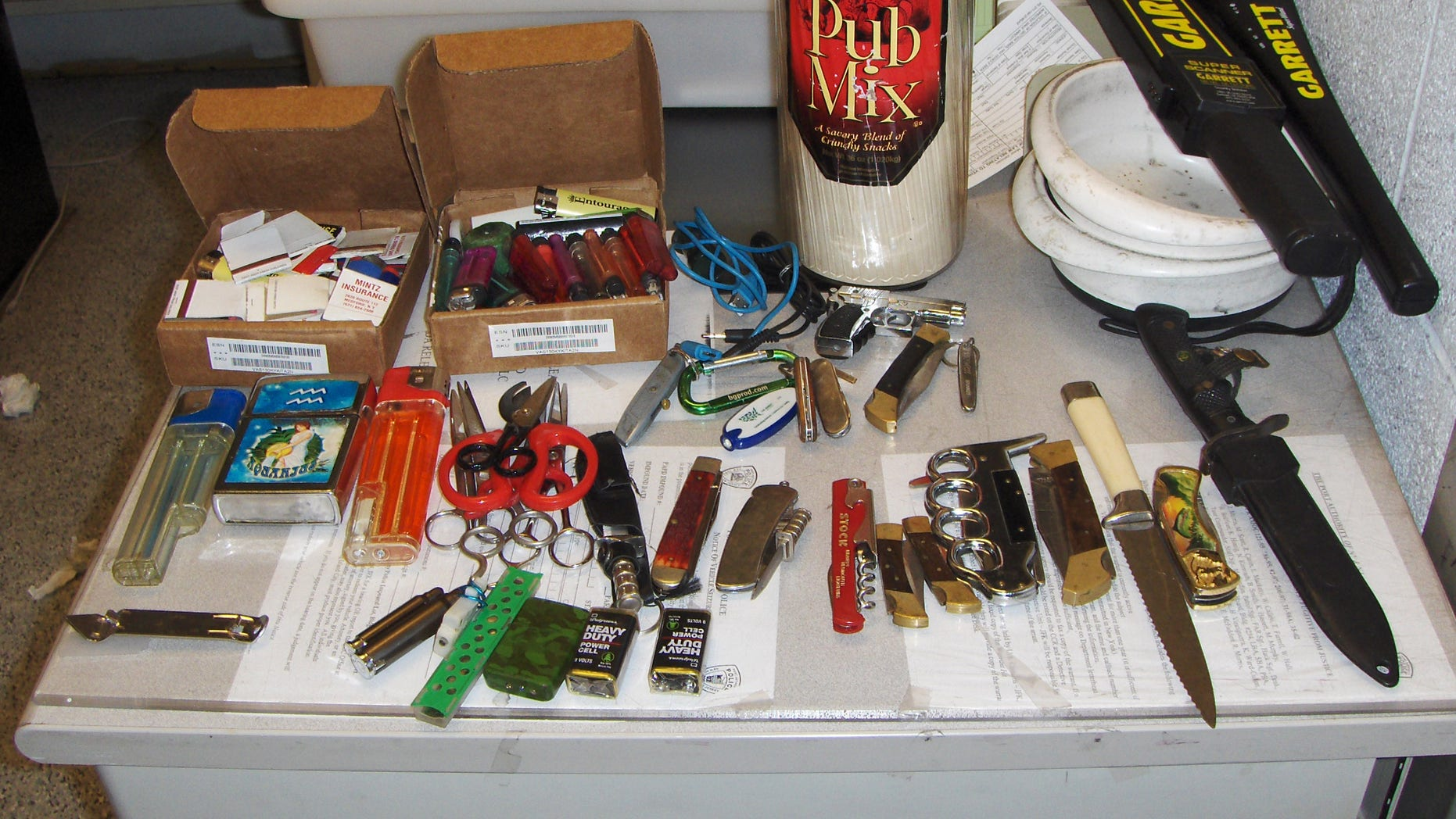 In this photo provided by the Police Department of the Port Authority of New York and New Jersey, a collection of large knives, cigarette lighters, scissors and matches fill a table at the Port Authority Police facility located in the John F. Kennedy International Airport in the Brooklyn Borough of New York, Saturday, Oct. 19, 2013. The items were sized after an airport baggage screener noticed the items in a person's carry-on bag. The Port Authority Police arrested Timothy Schiavo, Jr., 29, Patchogue NY and charged him with criminal possession of a weapon. (AP Photo/Port Authority Police Department of New York and New Jersey)