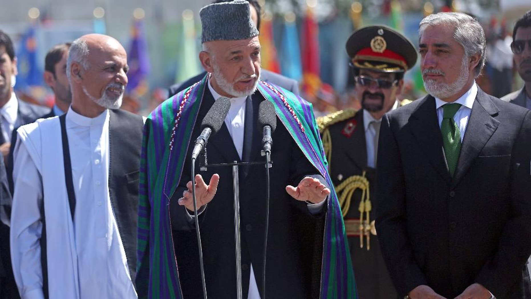 Afghan President Hamid Karzai, center, speaks in  front of local and international media representatives as presidential candidates Abdullah Abdullah, right, and Ashraf Ghani Ahmadzai, left , listen during the Independence Day ceremony in Kabul, Afghanistan, Tuesday, Aug. 19, 2014. King Amanullah won the country's independency from Britain in 1919. (AP Photo/Massoud Hossaini)