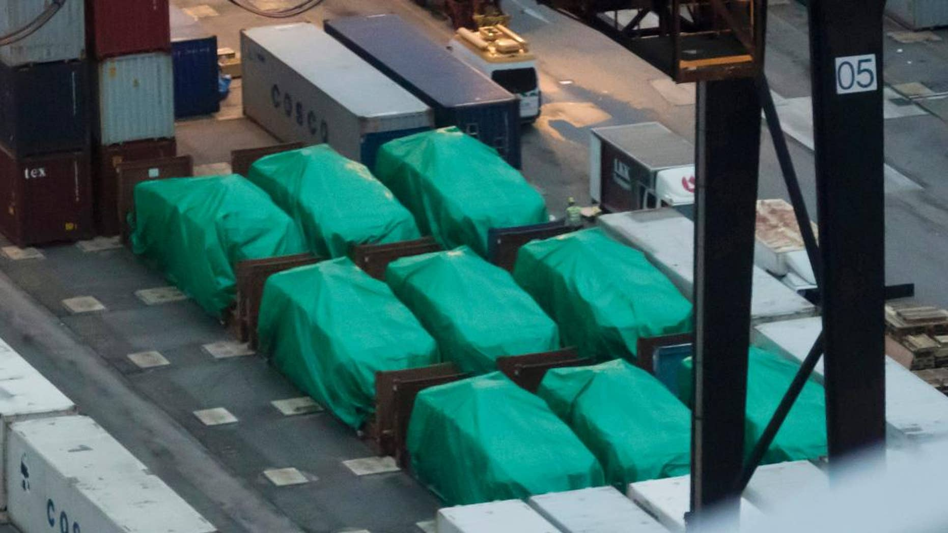 FILE - In this Thursday, Nov. 24, 2016, file photo, nine covered eight-wheeled Singapore-made Terrex infantry carrier vehicles are seized at a container terminal in Hong Kong. Authorities say nine armored personnel carriers belonging to Singapore that were seized in the Chinese territory of Hong Kong will be returned. (AP Photo/Kin Cheung, File)