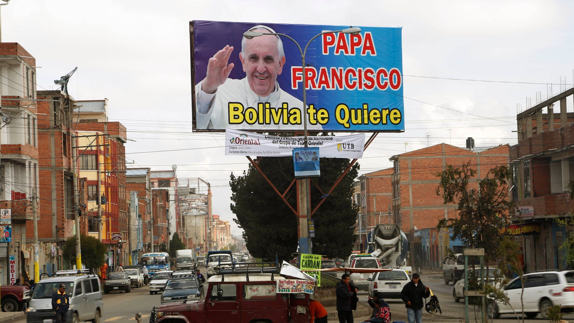 "FILE - In this April 16, 2015, file photo, street food vendors set up their stand under a billboard featuring Pope Francis with a message that reads in Spanish; ""Pope Francis, Bolivia loves you,"" in El Alto, Bolvia. Pope Francis' three-nation trip to South America that includes Ecuador, Bolivia and Paraguay, is set for July 6-12, though he will only spend six hours in Bolivia's capital due to the altitude, church officials say. (AP Photo/Juan Karita, File)"