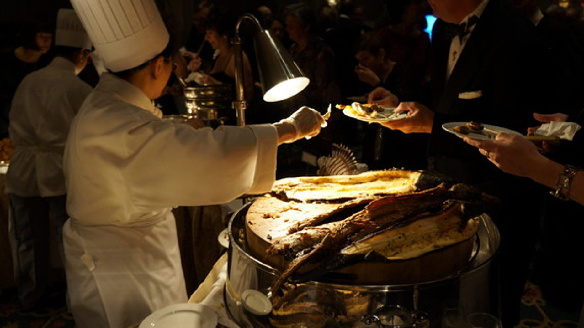 The adventurous hors d'oeuvres have become a staple of the glitzy gala, where astronauts and archaeologists rub shoulders with oceanographers and nature photographers. Shown here, a chef serves snakehead fish.