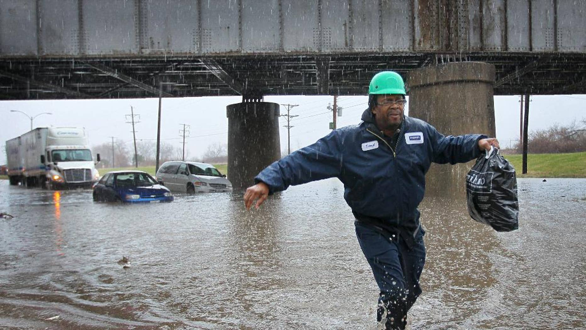 Darryl Hamilton walks away from his minivan stuck in floodwater in St. Louis on Wednesday, April 2, 2014. Three vehicles became stuck in the high water caused by a downpour. Everyone in the vehicles was able to walk out of the water on their own or were helped by police to dry land. (AP Photo/St. Louis Post-Dispatch, David Carson) (AP Photo/St. Louis Post-Dispatch, )  EDWARDSVILLE INTELLIGENCER OUT; THE ALTON TELEGRAPH OUT.