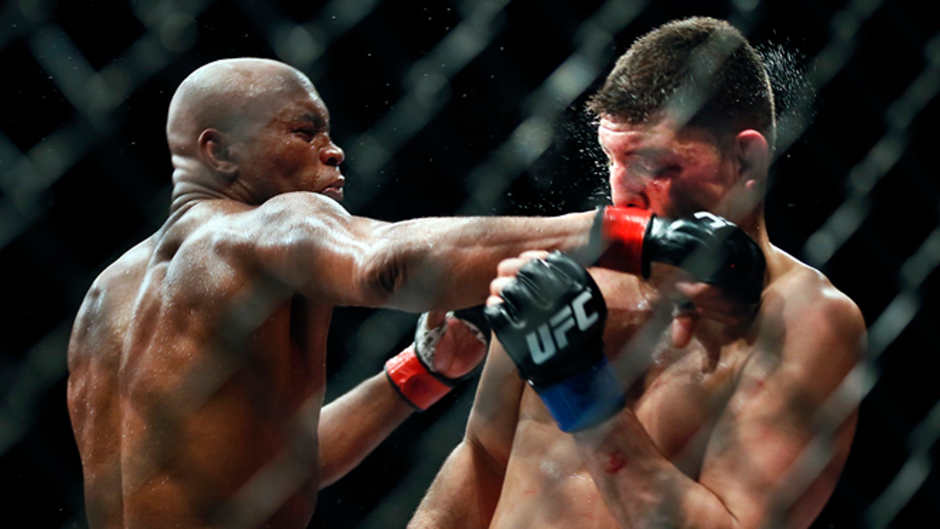 Middleweight Anderson Silva draws a fist across the face of Nick Diaz during their fight at the MGM Grand Garden Arena in Las Vegas on Saturday, Jan. 31, 2015. (AP Photo/Las Vegas Sun/LE Baskow)