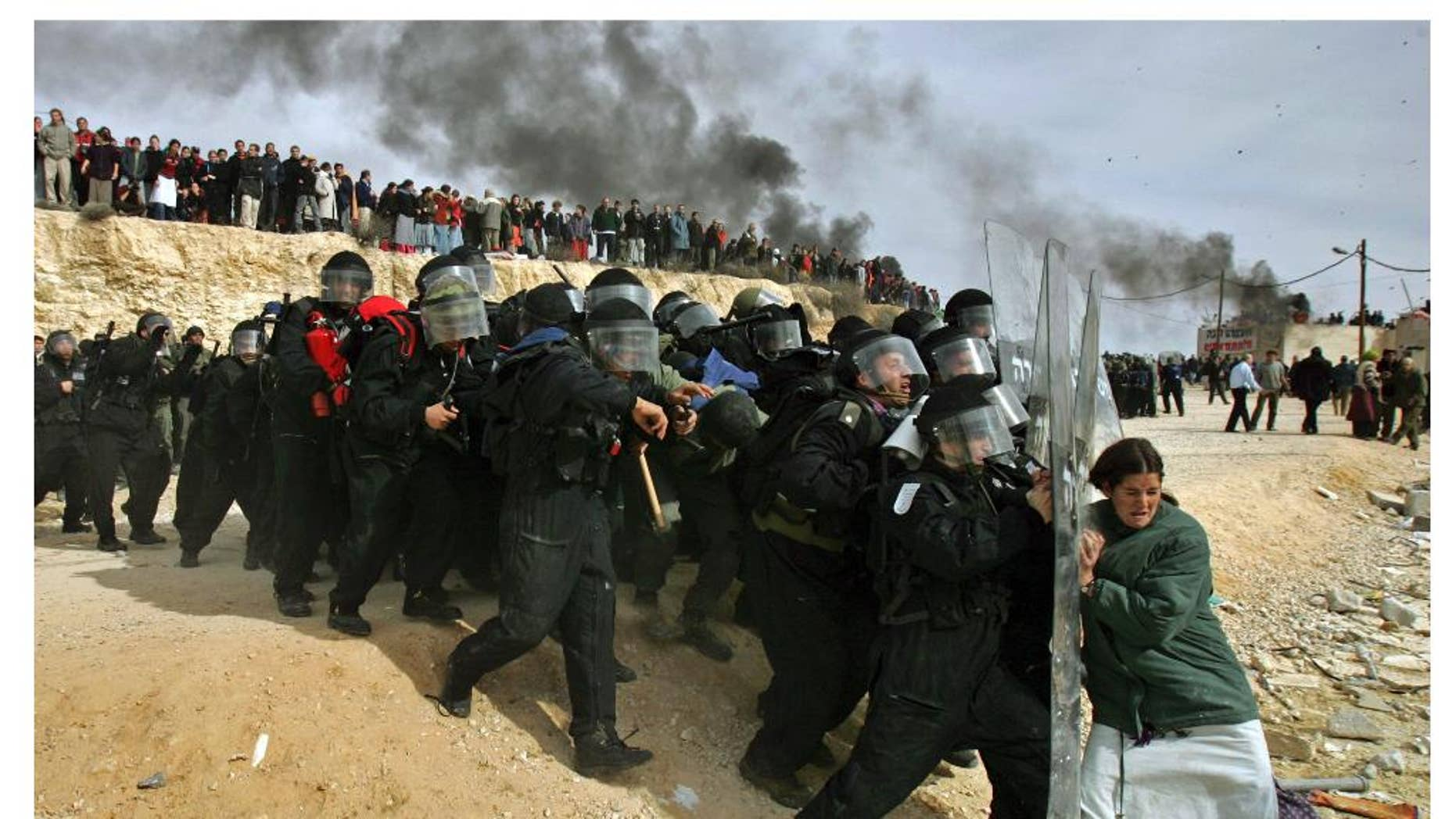 This combination of photos by Oded Balilty shows his Pulitzer Prize winning photograph of Israeli settlers challenging security forces at the West Bank outpost of Amona on Feb. 1, 2006, top, and at bottom Israeli settlers battling eviction from the same outpost exactly eleven years later, on Wednesday, Feb. 1, 2017. (AP Photo/Oded Balilty)