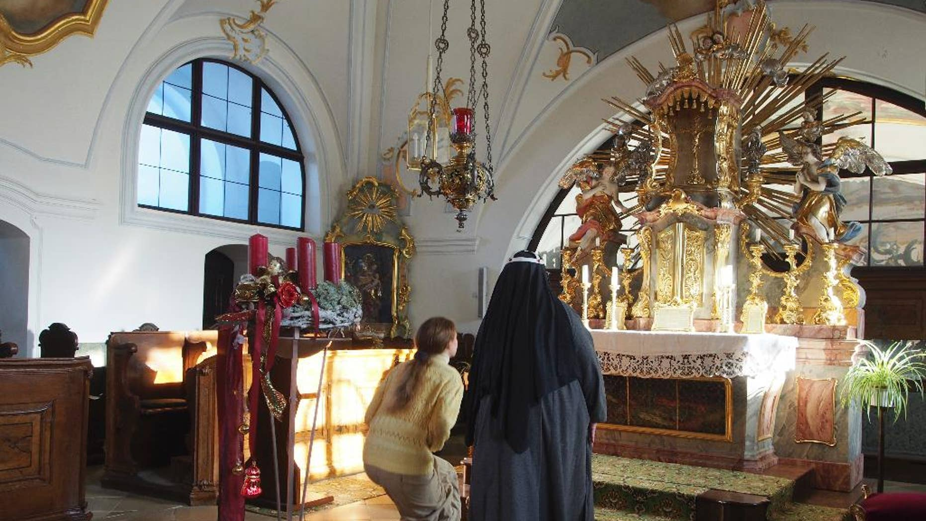 FILE -  In this Dec. 6, 2016 file photo Sister Apollonia, right, and Postulant Claudia Schwarz kneel in front of the altar of the chapel of the abbey in Altomuenster, Germany. Bavarian Catholic church authorities said Thursday, Jan. 19, 2017 they have closed Germany's last Bridgettine Order abbey at the request of the Vatican _ renewing concerns about what will happen to the property, including a precious library, which now goes to the local diocese.  (AP Photo/David Rising, file)