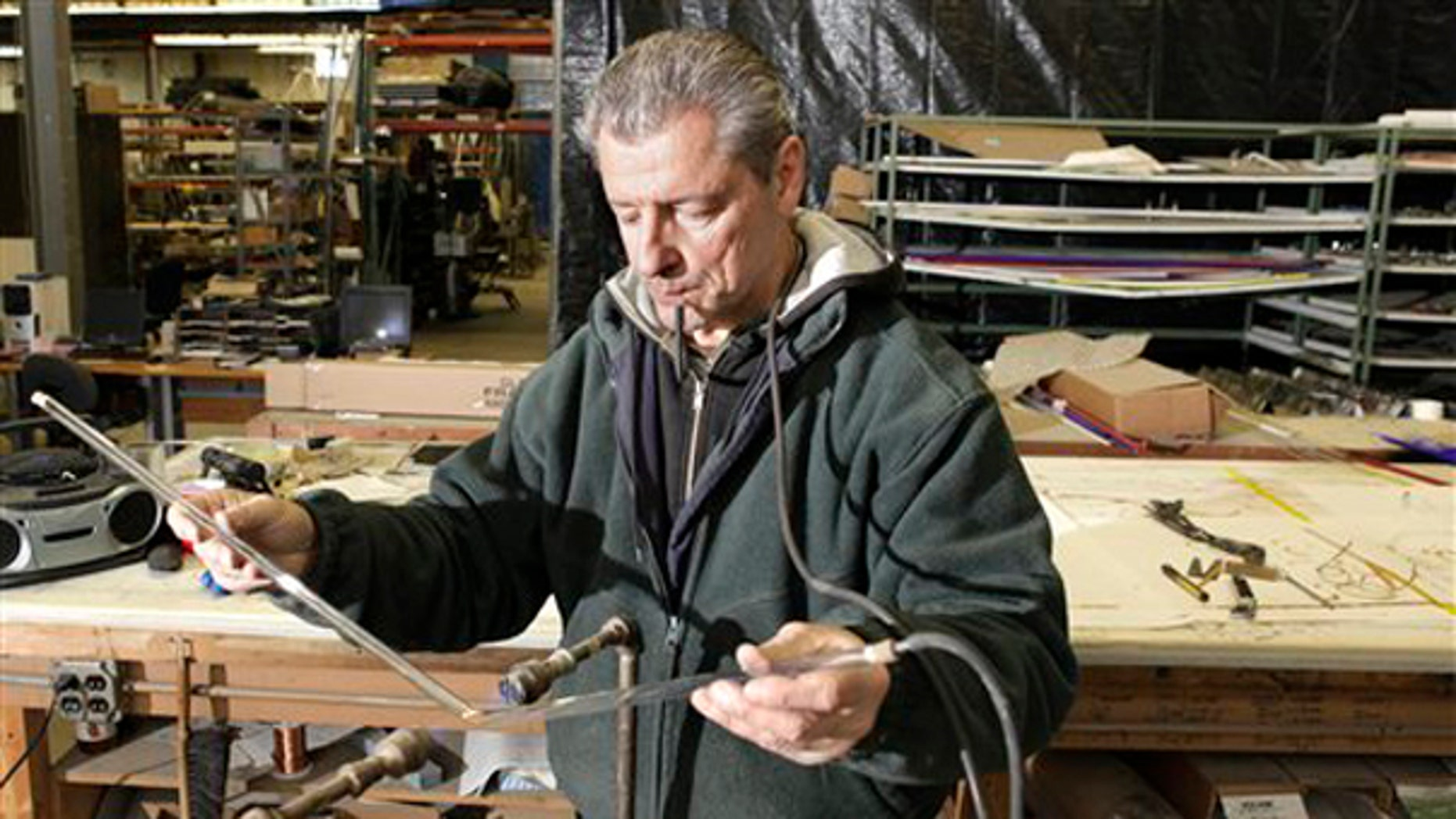 In this photo made Jan. 13, 2010, Rick Westover bends neon tubing for a sign at Glavin Industries in Solon, Ohio. (AP)