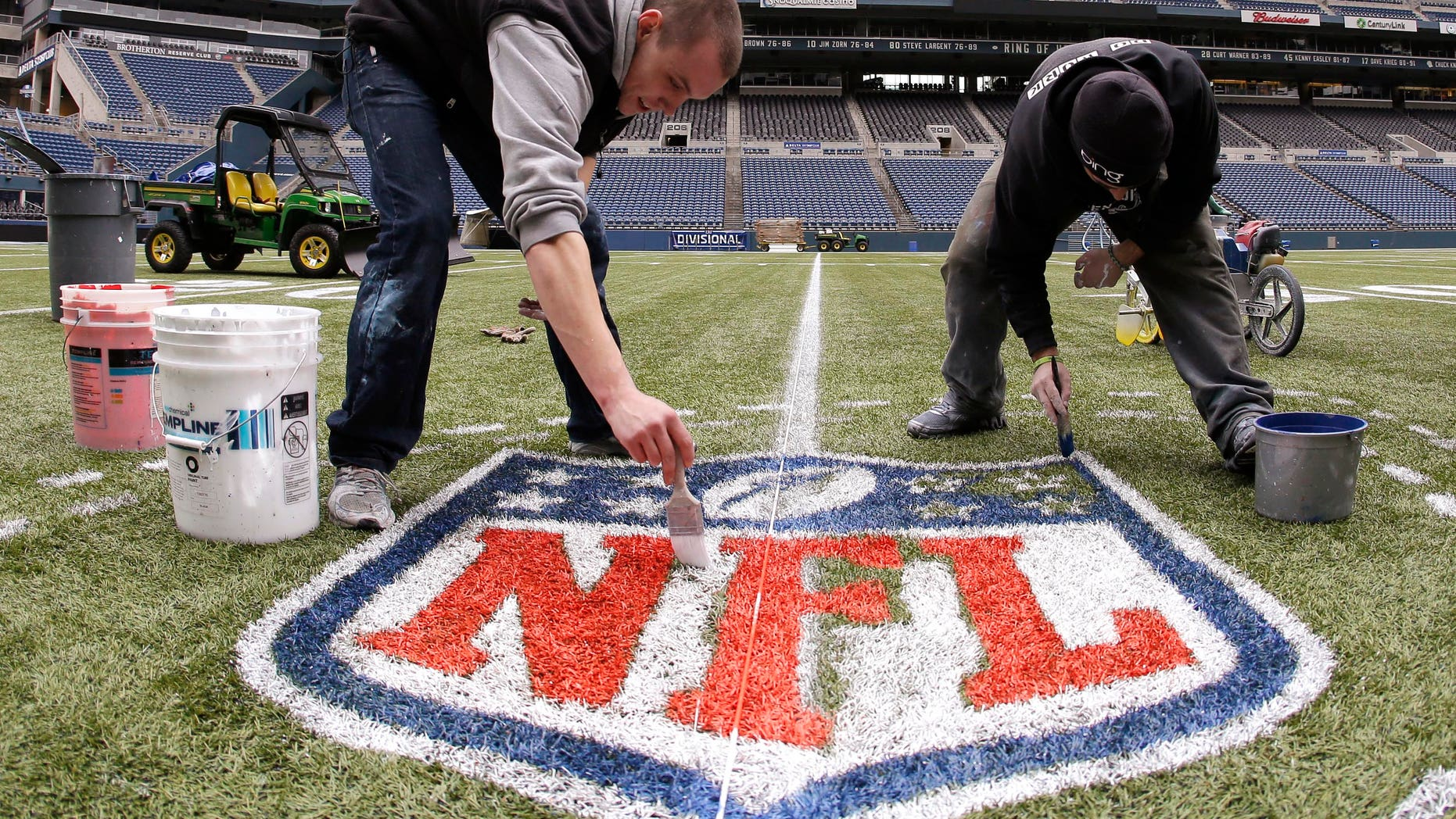 In this photo made with a fisheye lens, Austin Amon, left, and Ryan Johnson, right, paint an NFL championship logo Tuesday, Jan. 14, 2014, in Seattle as they prepare CenturyLink Field for Sunday's NFL football NFC championship game between the Seattle Seahawks and the San Francisco 49ers. (AP Photo/Ted S. Warren)