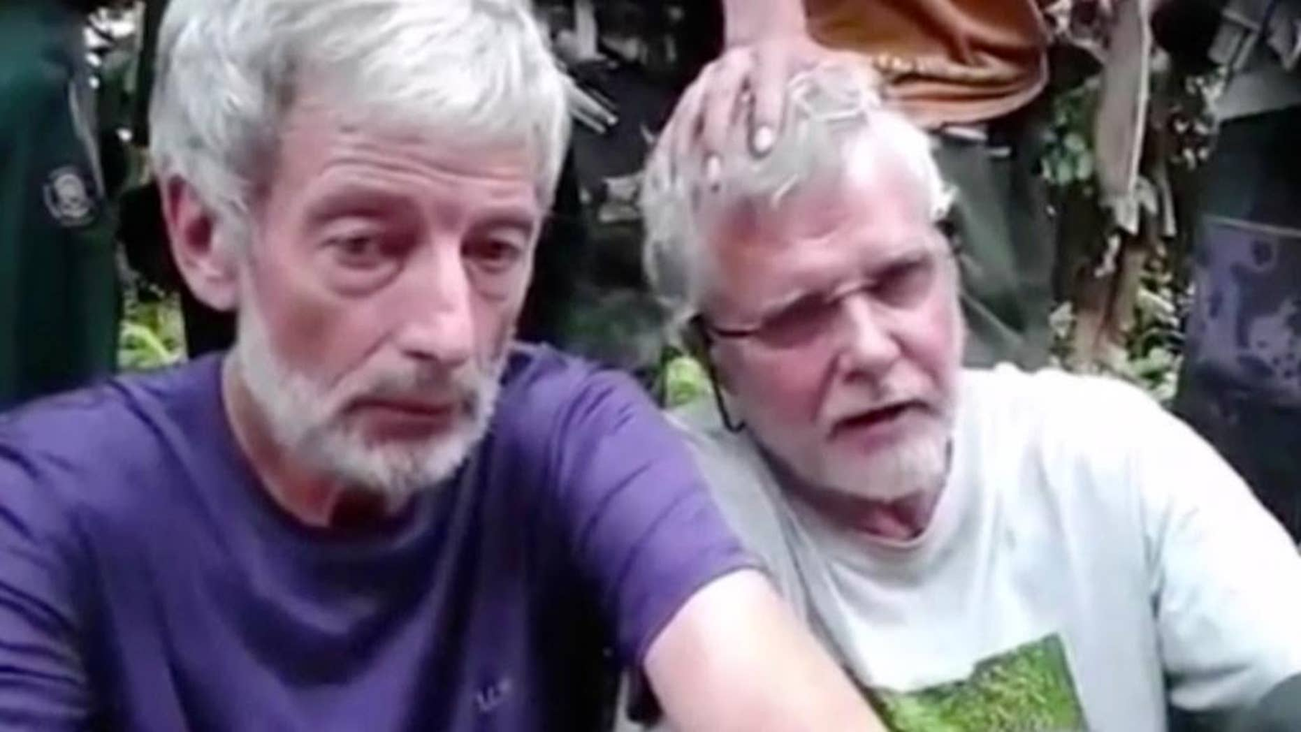 FILE - This file image made from undated militant video, shows Canadians Robert Hall, left, and John Ridsdel, right. With a black Islamic State group-style flag as a backdrop, Abu Sayyaf fighters beheaded Canadian hostage Hall on southern Jolo island on Monday, June 13, 2016,  after a ransom deadline passed.  Enraged by the beheading of a second Canadian hostage by ransom-seeking Abu Sayyaf extremists, Philippine troops pressed a major offensive in the south Tuesday, June 14, 2016,  but there was no sign of an end to the small but brutal insurgency that a new president will inherit in about two weeks. (Militant Video via AP Video, File) NO SALES, MANDATORY CREDIT