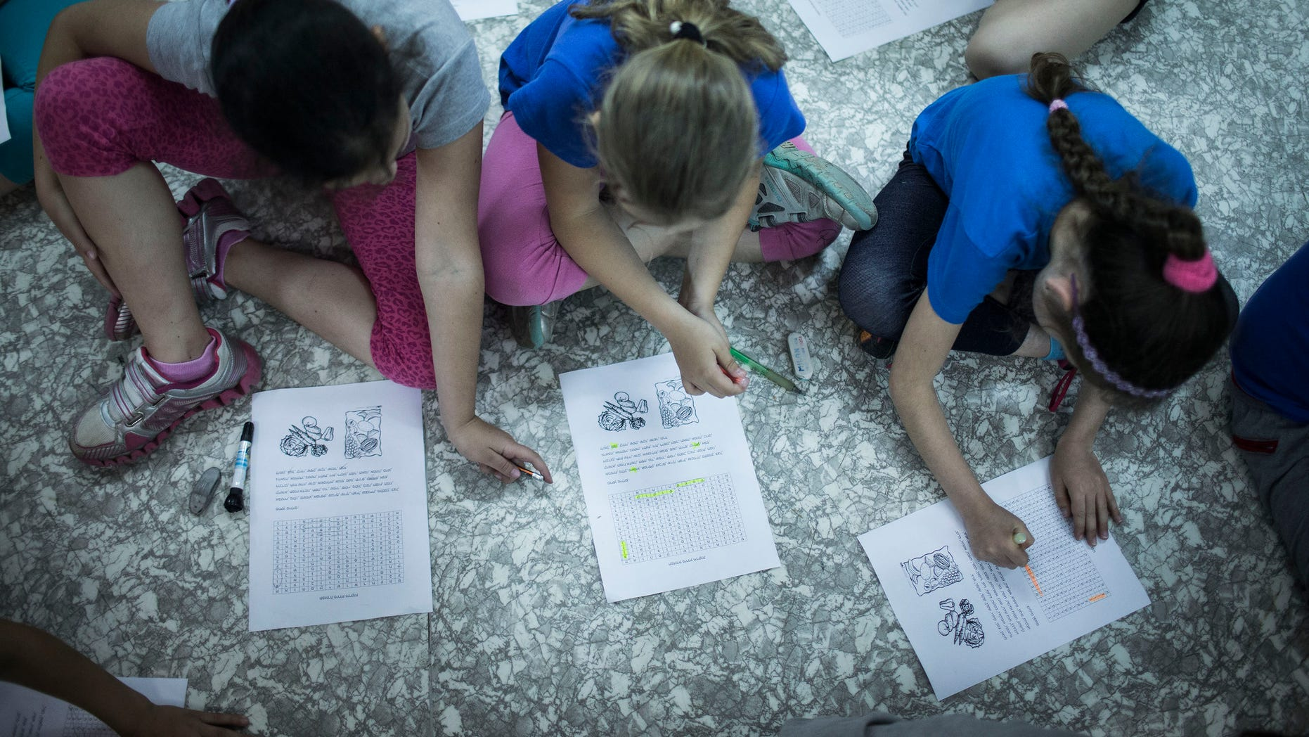 """NAZARETH-ILIT, ISRAEL - MAY 27 : Israeli schoolchildren do classwork while in a bomb shelter at their school during the Home Front drill """"Turning Point 7"""" on May 27, 2013 in Nazareth-Ilit, Israel. The nationwide exercise tests the civilian population's response to a possible massive rocket attack from three fronts. (Photo by Ilia Yefimovich/Getty Images)"""
