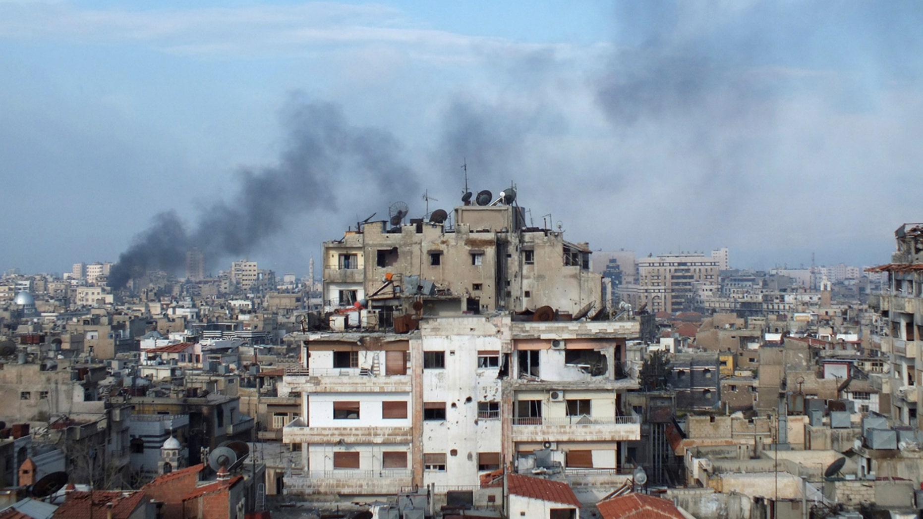 Smoke rises from a building in the city of Homs, Syria, in this file photo from March 2013.