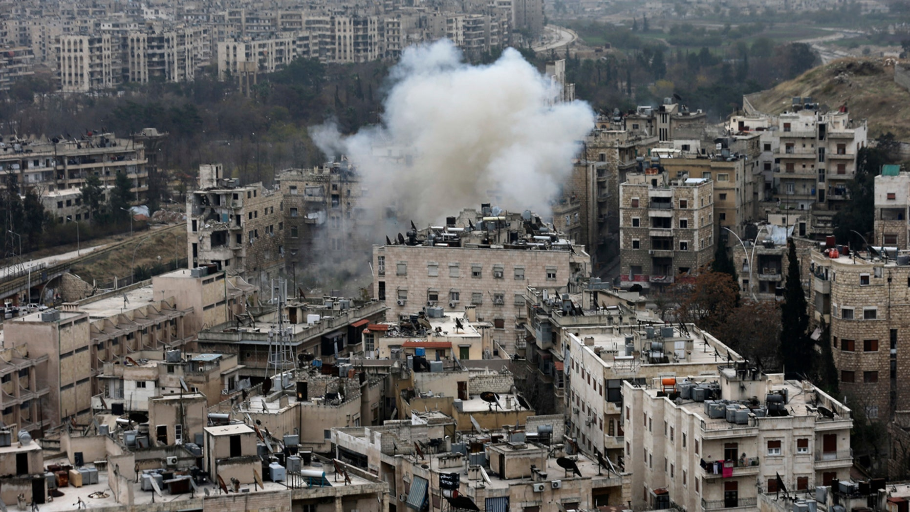 Smoke rises after rebel fighters launch a mortar shell on residential neighborhood in west Aleppo, Syria, Monday, Dec. 5, 2016.