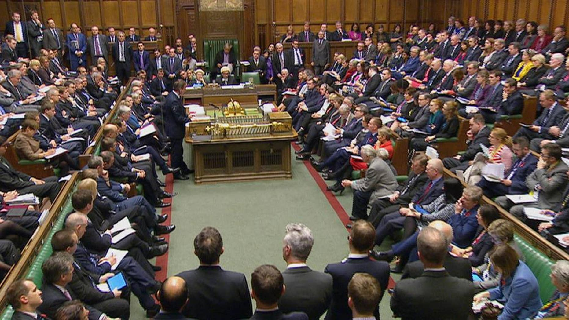 British Prime Minister David Cameron, standing centre left, talks to lawmakers inside the House of Commons in London during a debate on launching airstrikes against Islamic State extremists inside Syria, Wednesday, Dec. 2, 2015. The parliamentary vote is expected Wednesday evening.  Opposition Labour Party leader, Jeremy Corbyn, looks at papers sitting centre right opposite Cameron, who opposes any expansion of Britain's military role. (Parliamentary Recording Unit via AP Video) TV OUT - NO ARCHIVE