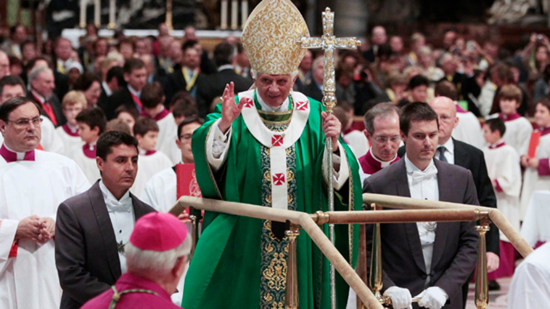 Oct. 16: Pope Benedict XVI stands on a mobile platform as he leaves St. Peter's Basilica at the end of a mass at the Vatican.