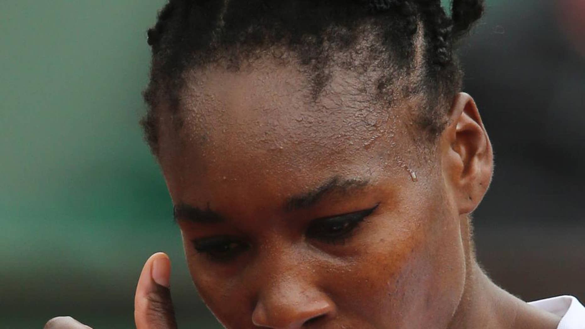 Venus Williams of the U.S. wipes away some beads of sweat during the second round match of the French Open tennis tournament against Slovakia's Anna Schmiedlova at the Roland Garros stadium, in Paris, France, Wednesday, May 28, 2014. (AP Photo/David Vincent)