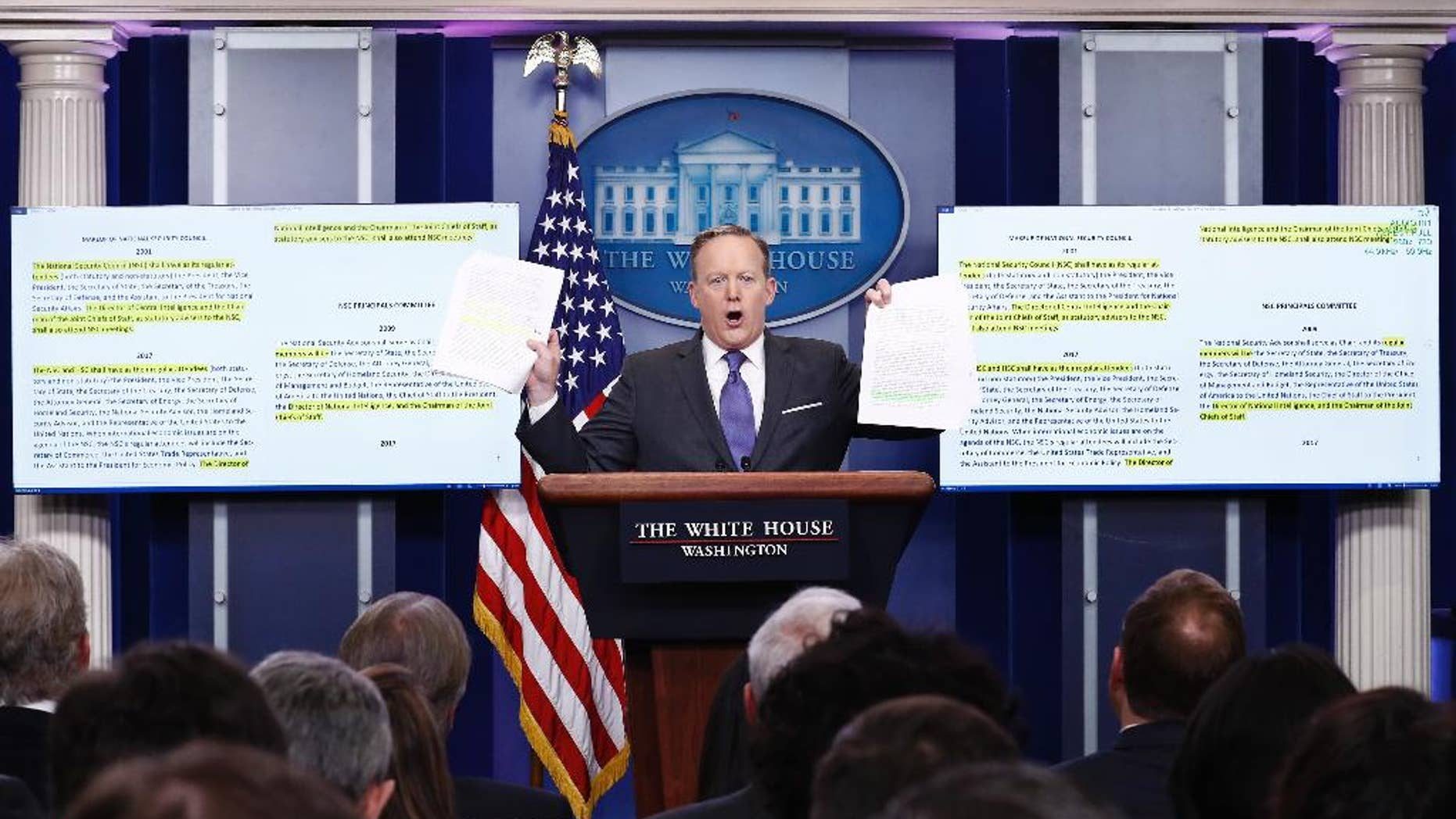 White House press secretary Sean Spicer holds up paperwork about the National Security Council as he speaks during the daily news briefing at the White House in Washington, Monday, Jan. 30, 2017. (AP Photo/Carolyn Kaster)