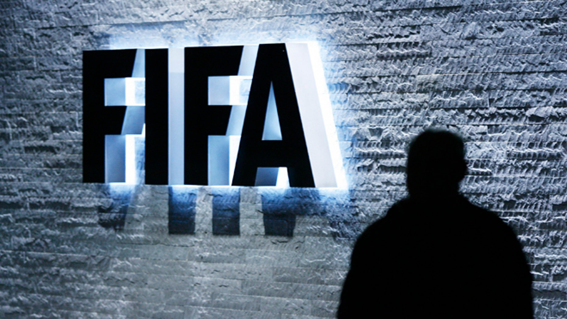 FILE - In this Oct. 29, 2007 file photo, a person stands next to the FIFA logo at the FIFA headquarter in Zurich, Switzerland. The Swiss Federal Office of Justice said six soccer officials have been arrested and detained pending extradition at  the request of U.S. authorities ahead of the FIFA congress in Zurich. In a statement Wednesday, May 27, 2015, the FOJ said U.S. authorities suspect the officials of having received paid bribes totaling millions of dollars.  (Steffen Schmidt/Keystone via AP, File)