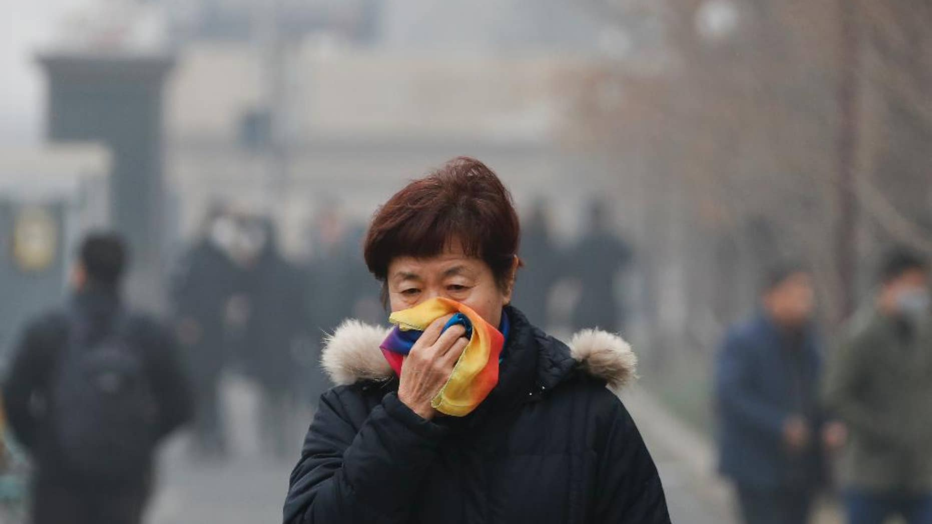 FILE - In this Tuesday, Dec. 20, 2016, file photo, a woman uses a scarf to cover her mouth for protection against the air pollution as she walks on a street in Beijing, China. Beijing will spend $2.7 billion to fight air pollution in the capital this year, state media reported Thursday. (AP Photo/Andy Wong, File)