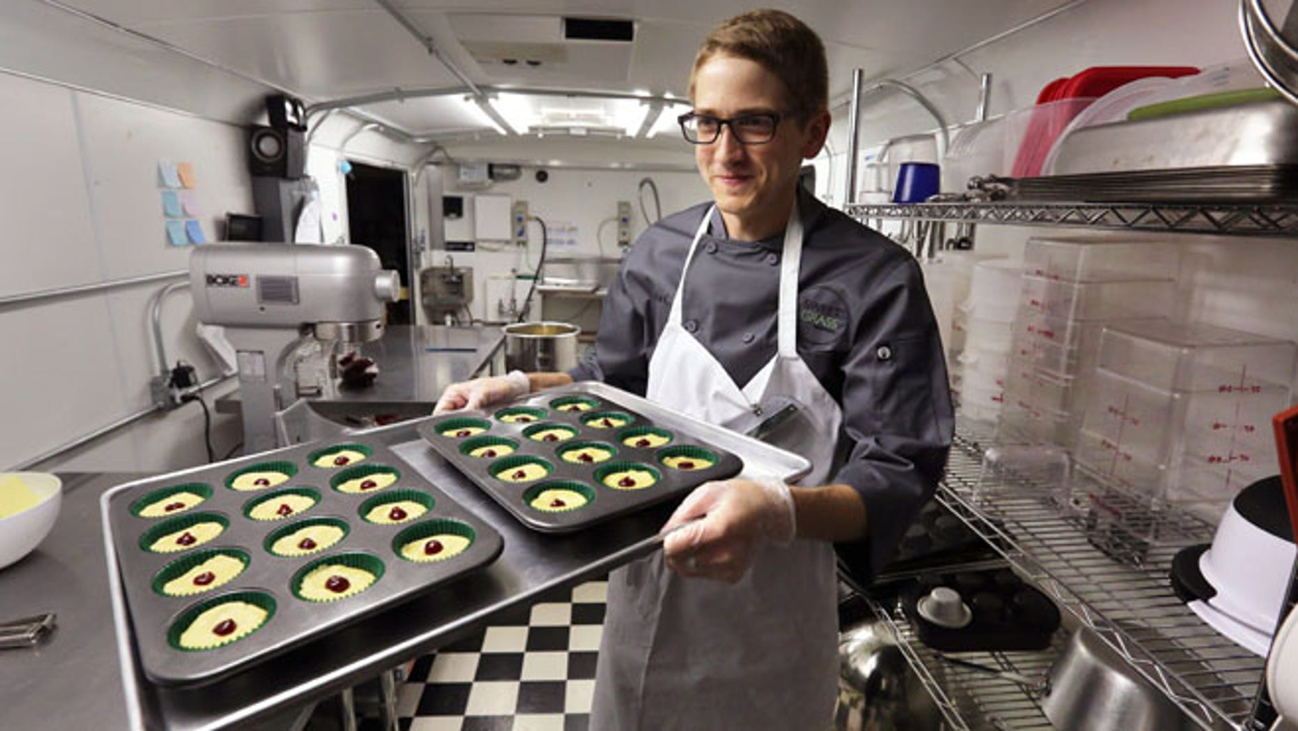 June 19, 2014: Chef Alex Tretter carries a tray of cannabis-infused peanut butter and jelly cups to the oven for baking at Sweet Grass Kitchen, a well-established Denver-based gourmet marijuana edibles bakery which sells its confections to retail outlets throughout the state.
