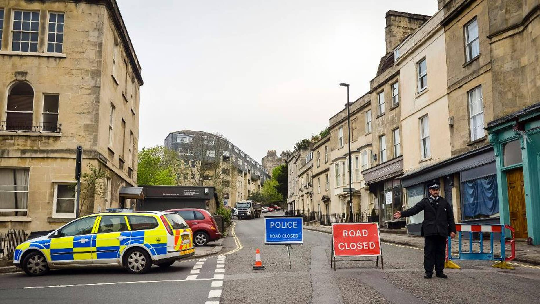 Police divert away traffic from an exclusion zone set up after contractors unearthed a Second World War shell in Bath, England, Friday, May 13, 2016. Hundreds of people have been told to leave homes and businesses in the English city of Bath after a 500-pound (225-kilogram) unexploded World War II shell was found under a school playground. Police evacuated residents for 300 meters (yards) around the device, found during construction work at the disused Royal High School. Some spent the night at a local racecourse. (Ben Birchall/PA via AP)      UNITED KINGDOM OUT        -     NO SALES       -       NO ARCHIVES