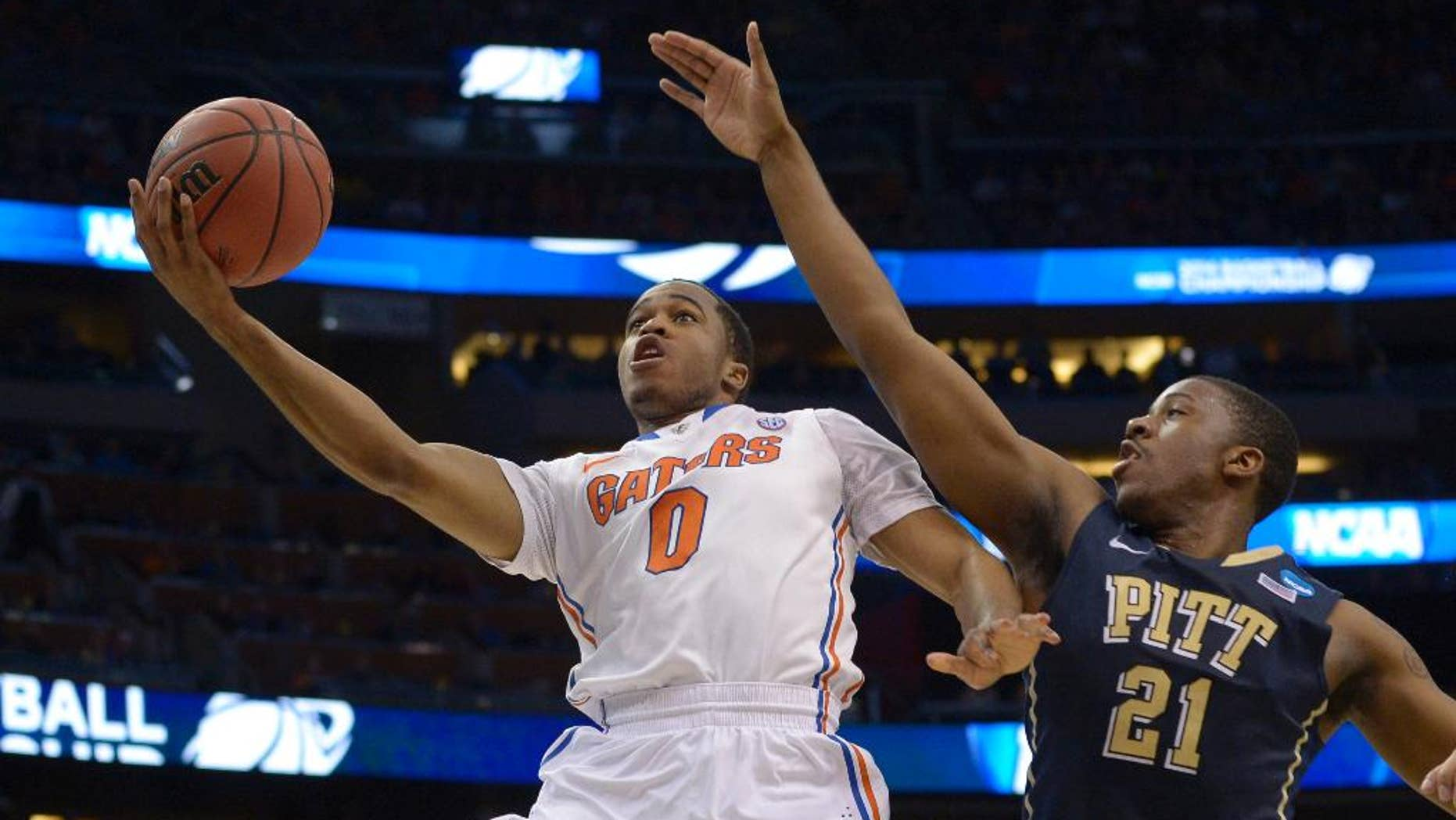 Florida guard Kasey Hill (0) drives to the basket as Pittsburgh forward Lamar Patterson (21) defends during the first half in a third-round game in the NCAA college basketball tournament  Saturday, March 22, 2014, in Orlando, Fla. (AP Photo/Phelan M. Ebenhack)