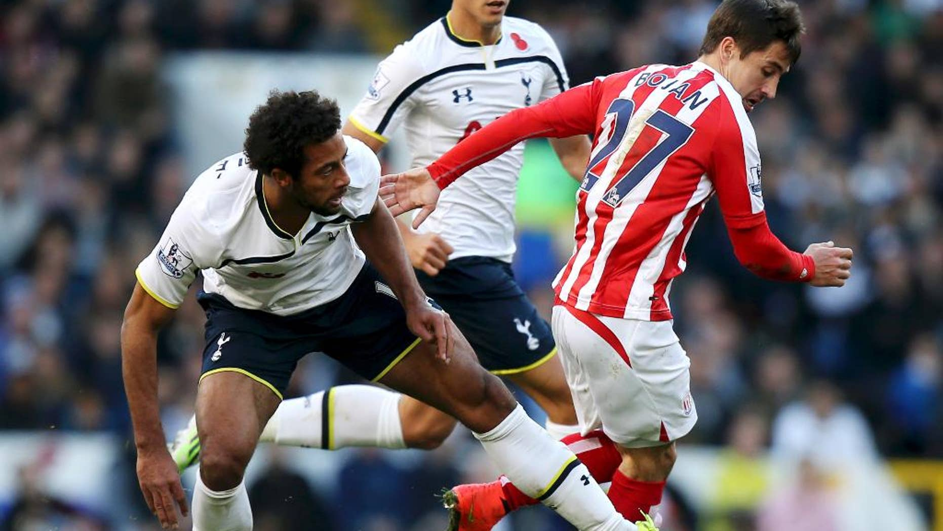 Stoke City's Bojan Krkic, right, is tackled by Tottenham Hotspur's Mousa Dembele, during their  English Premier League soccer match at White Hart Lane in London, Sunday Nov. 9, 2014. (AP Photo / John Walton, PA) UNITED KINGDOM OUT - NO SALES - NO ARCHIVES