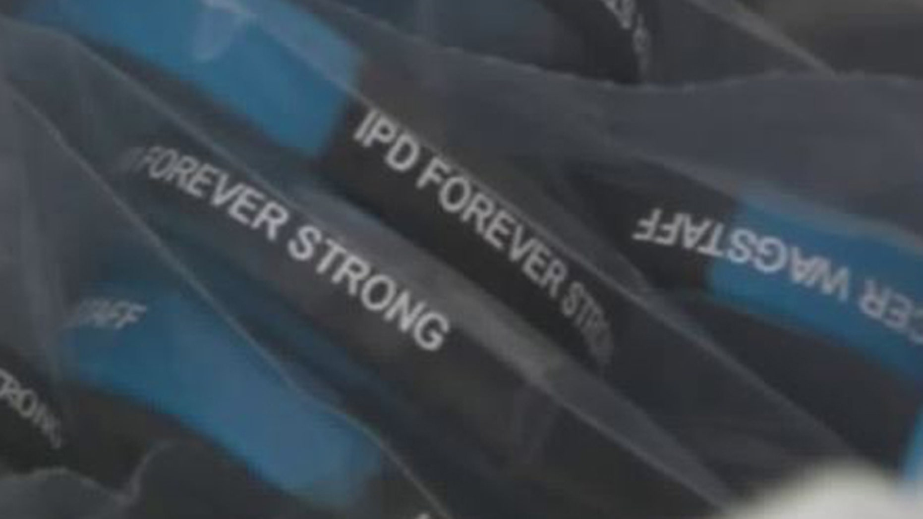 """The wristbands read """"IPD Forever Strong,"""" with the officer's name."""