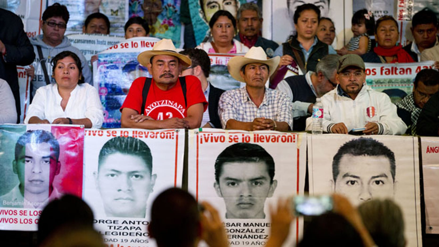 Relatives of 43 missing students, accompanied by their spokesman and human rights activists, take their seats during a press conference. (AP Photo/Rebecca Blackwell)