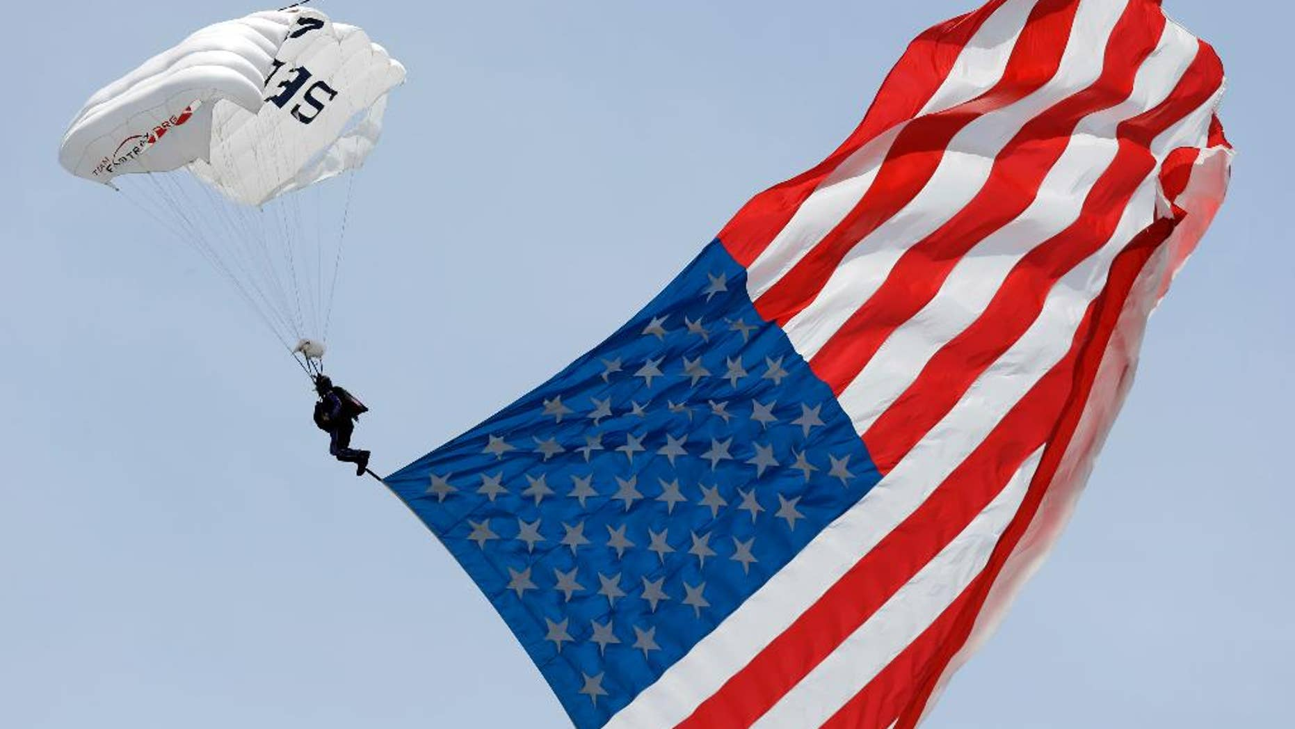 A parachutist descends into the Charlotte Motor Speedway prior to a NASCAR Xfinity Series auto race in Concord, N.C., Saturday, May 28, 2016. (AP Photo/Gerry Broome)