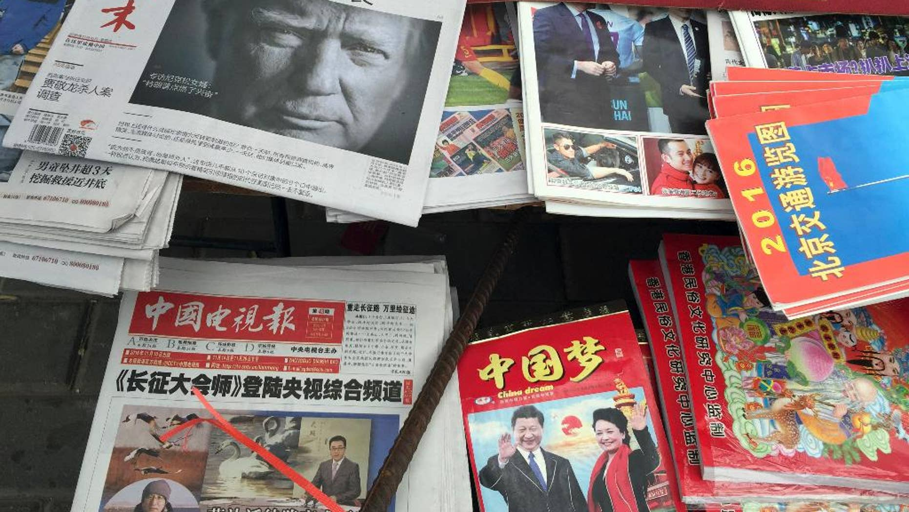 """A front page of a Chinese newspaper with a photo of U.S. President-elect Donald Trump and the headline """"Outsider counter attack"""" is displayed at a newsstand in Beijing, China, Thursday, Nov. 10, 2016. Trump is a mixed blessing for Chinese leaders. His threats to tear up trade deals and hike tariffs on Chinese goods could chill thriving commercial ties when Beijing is struggling to shore up economic growth. At the same time, Trump's suggestion he might reduce Washington's global strategic presence to focus on domestic issues would be a gift to Chinese leaders. They could expand their political and military profile in East Asia with less risk of conflict. (AP Photo/Ng Han Guan)"""