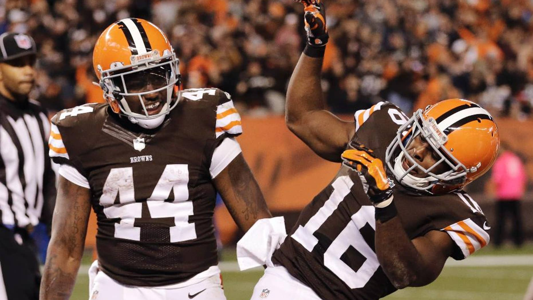 Cleveland Browns wide receiver Andrew Hawkins (16) celebrates running back Ben Tate's (44) 5-yard touchdown run in the fourth quarter of an NFL football game against the Oakland Raiders, Sunday, Oct. 26, 2014, in Cleveland. (AP Photo/Tony Dejak)