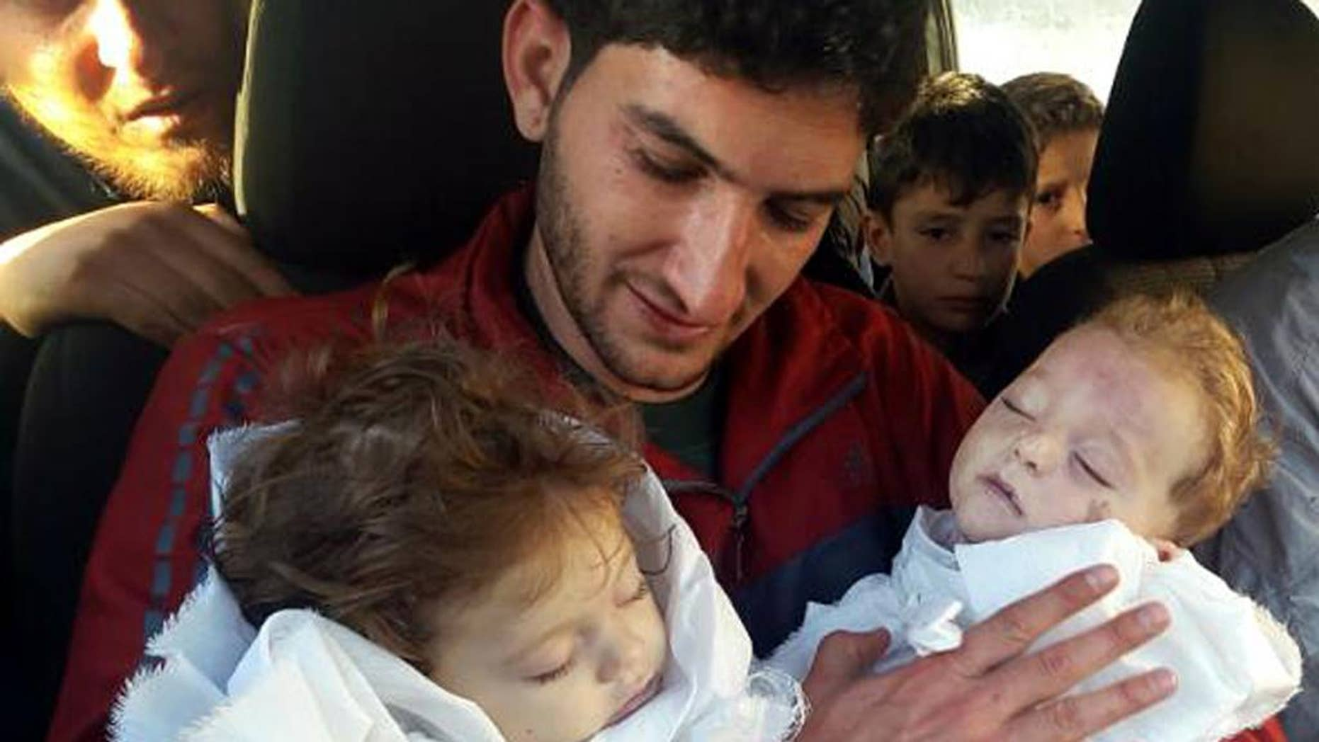 FILE - In this Tuesday, April 4, 2017, file photo, Abdul-Hamid Alyousef holds his twin babies who were killed by a chemical weapons attack, in Khan Sheikhoun in the northern province of Idlib, Syria. Alyousef also lost his wife, two brothers, nephews and many other family members in the attack that claimed scores of his relatives. New evidence presented by Human Rights Watch on Monday, May 1, indicates that the Syrian government used suspected nerve agents in four chemical weapons attacks since December including this one. (Alaa Alyousef via AP, File)