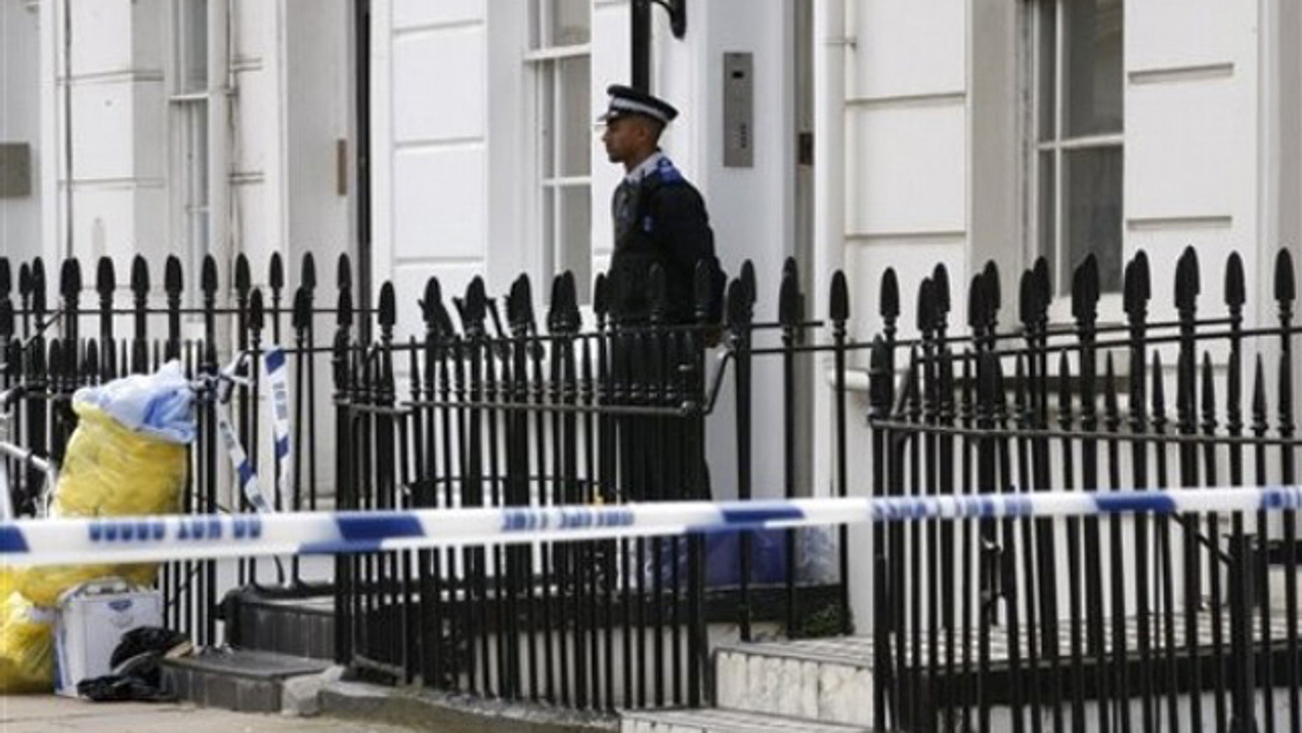 Aug. 25: A British Community Police Support Officer stands quard outside a house in central London, near the headquarters of MI6, where a man believed to be a British spy has been found dead in a flat.