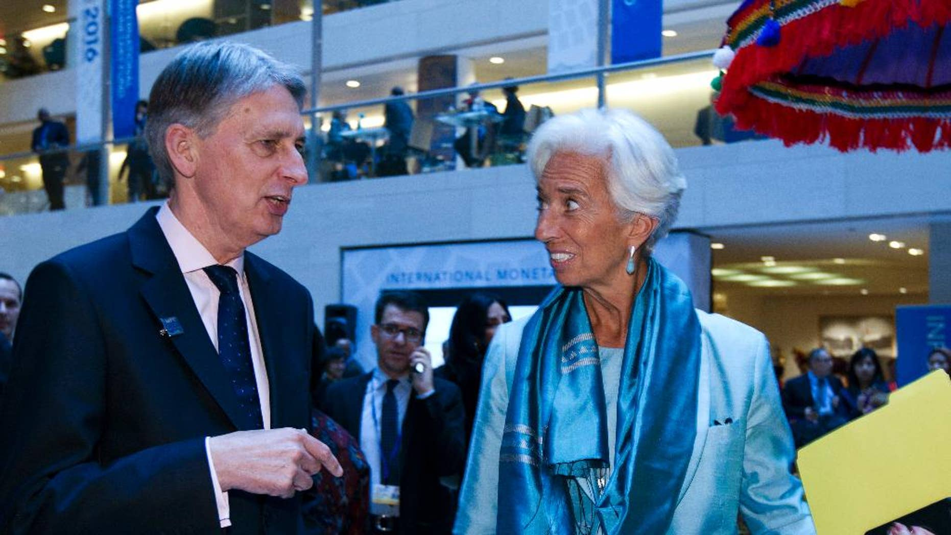 International Monetary Fund (IMF) Managing Director Christine Lagarde speaks with Chancellor of the Exchequer Philip Hammond after a news conference at World Bank/IMF Annual Meetings at IMF headquarters in Washington, Saturday, Oct. 8, 2016. ( AP Photo/Jose Luis Magana)
