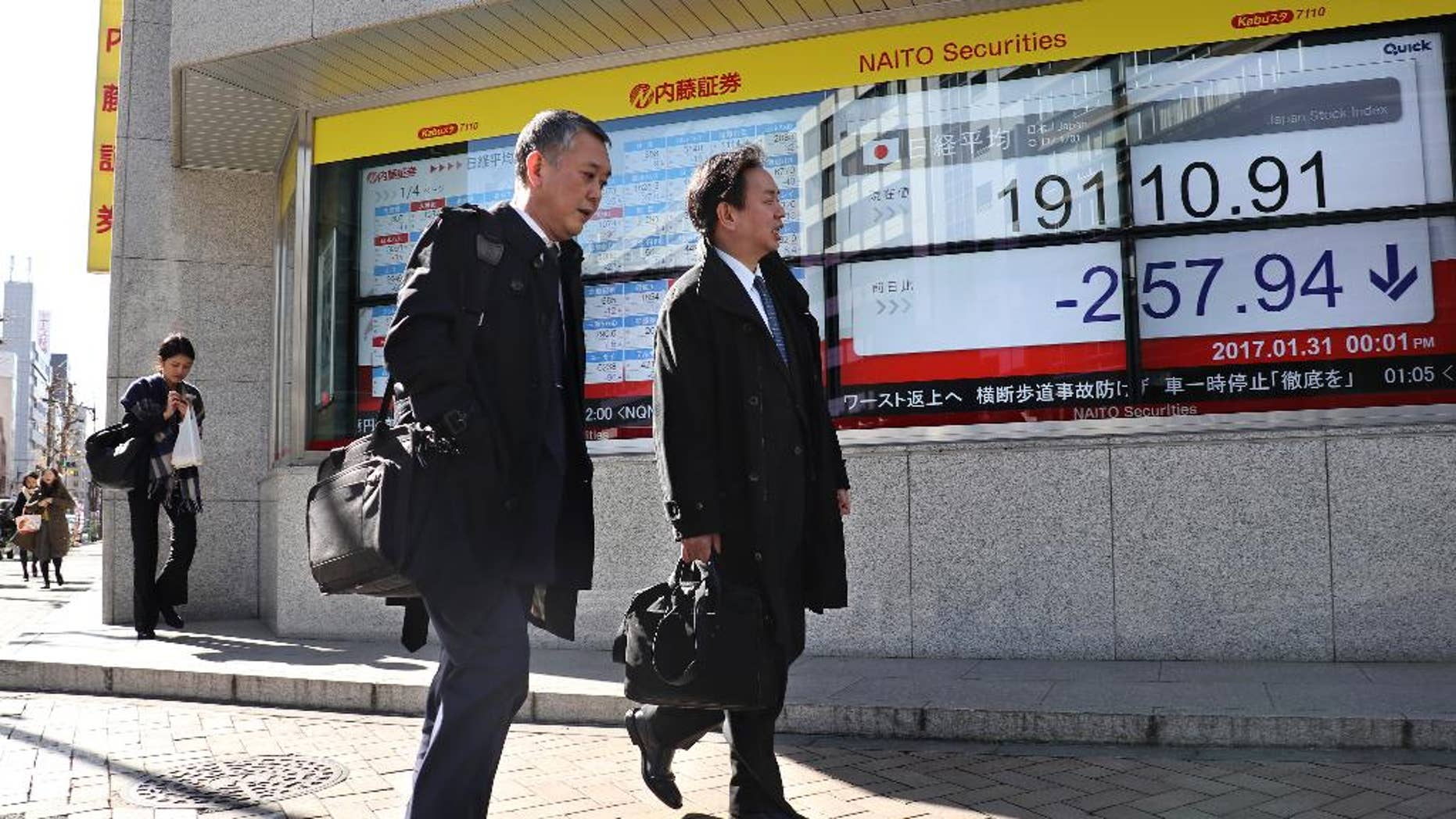 Men walk past an electronic stock indicator of a securities firm in Tokyo, Tuesday, Jan. 31, 2017. Asian shares slipped Tuesday, tracking a decline on Wall Street set off by jitters over President Donald Trump's travel ban. (AP Photo/Shizuo Kambayashi)