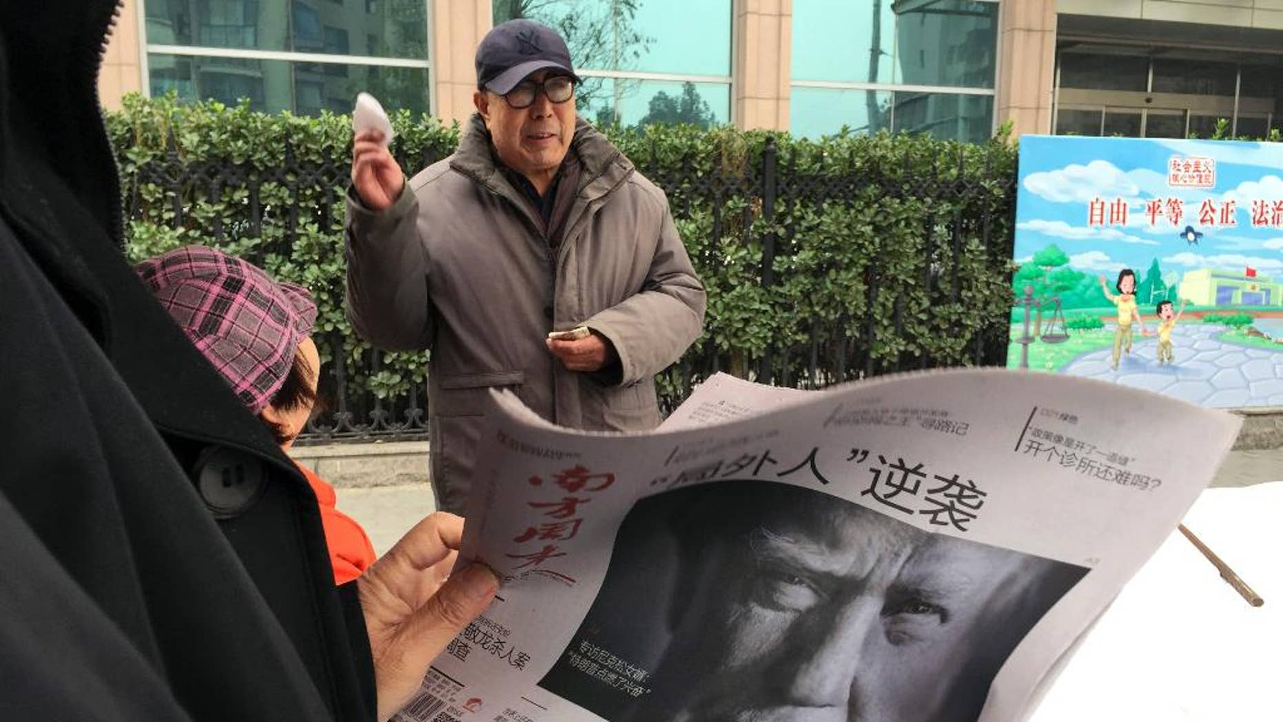 "FILE - In this Nov. 10, 2016 file photo, a Chinese man holds up a Chinese newspaper with the front page photo of U.S. President-elect Donald Trump and the headline ""Outsider counter attack"" at a newsstand in Beijing, China. China views a Trump presidency with less trepidation. Citizens of China's capital Beijing on Saturday are expressing doubts about U.S. President Donald Trump's ability to steer the U.S. economy and manage China-American relations. (AP Photo/Ng Han Guan, File)"